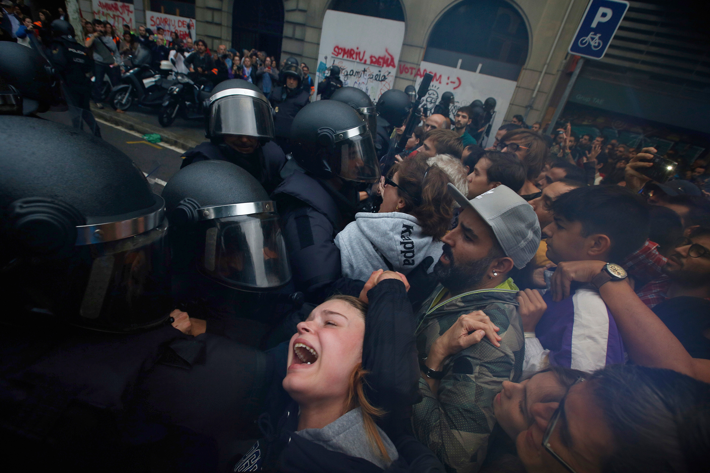 Spanish police push pro-referendum supporters outside a school assigned as a polling station in Barcelona on Oct. 1