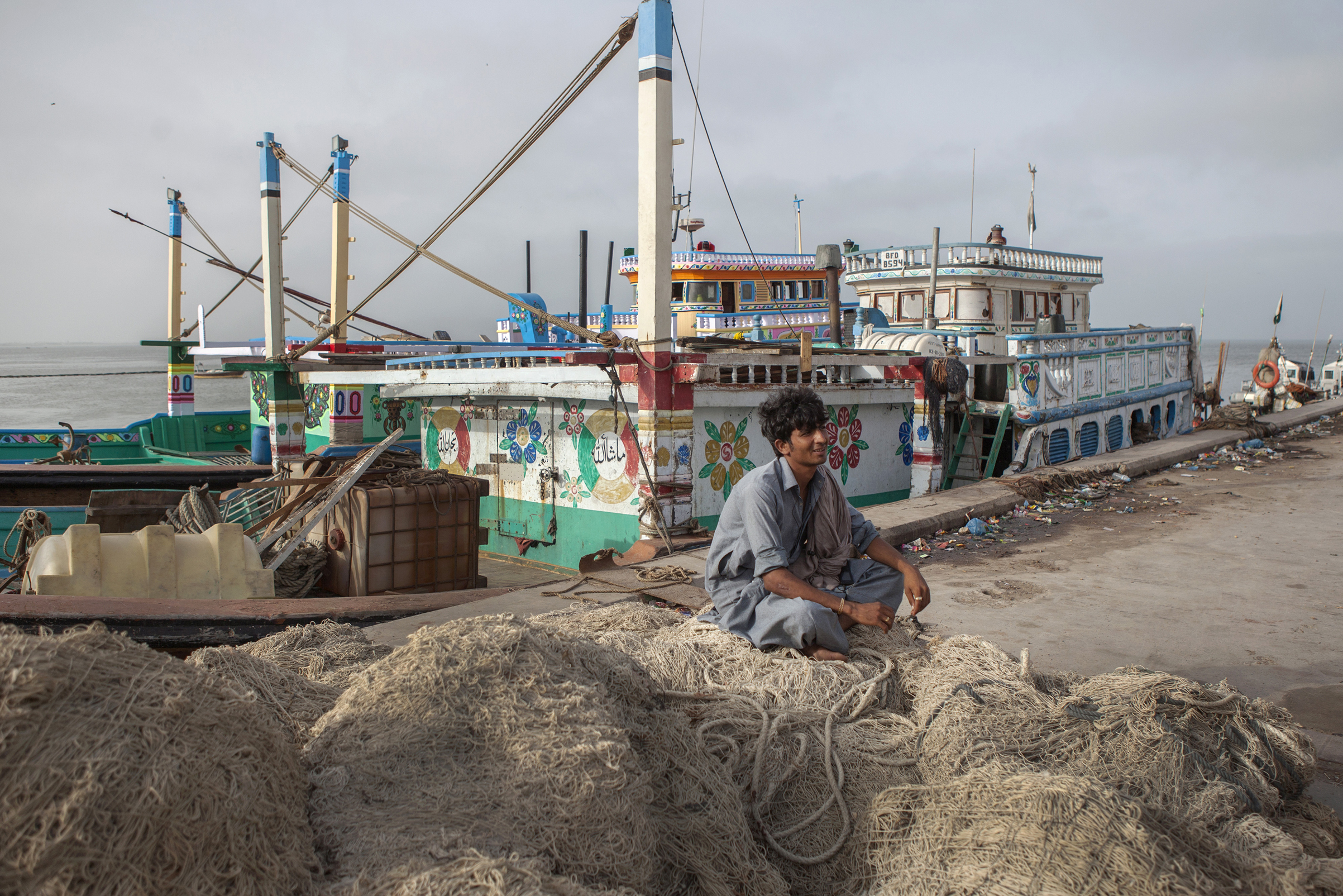 A fisherman sits on a pile of nets at a harbor in Gwadar, Balochistan, Pakistan, on Aug. 2, 2016. Gwadar is the cornerstone of China's project to rebuild the ancient trading route that connects China to the Arabian Sea, slicing through the Himalayas and crossing deserts and disputed territory to reach this ancient fishing port, about 500 miles by boat from Dubai.