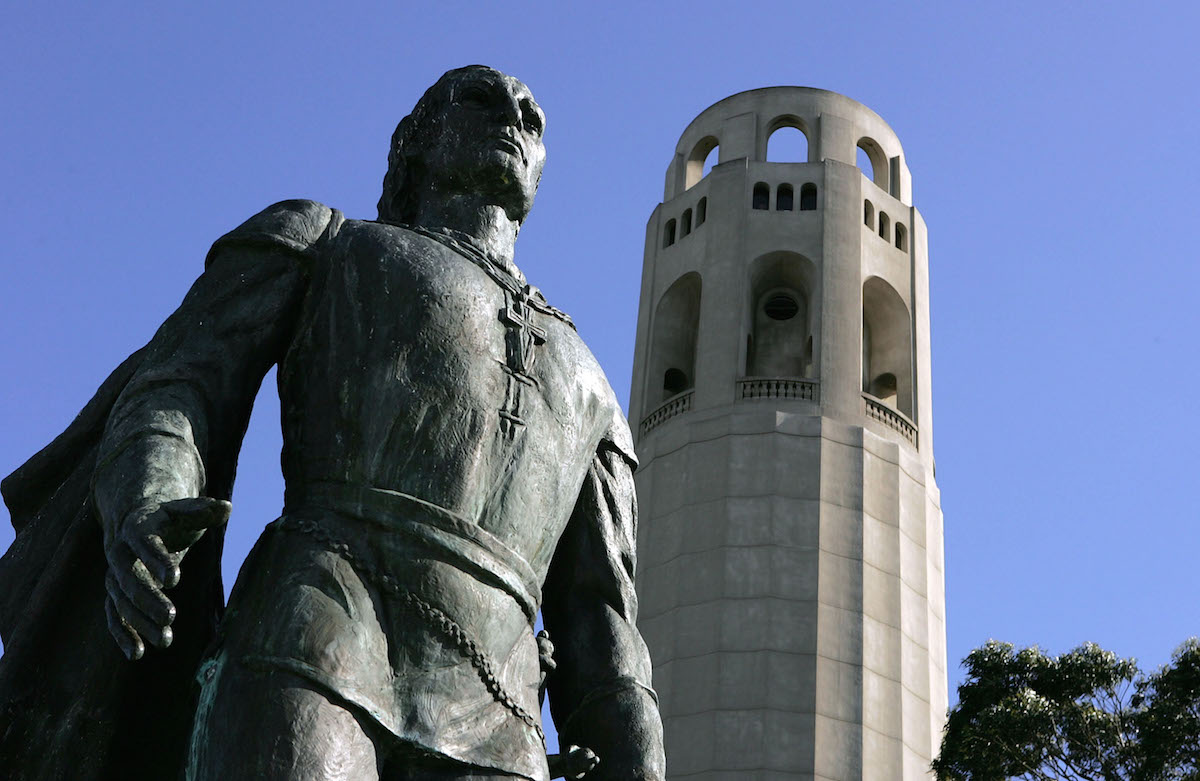 A statue of Christopher Columbus is seen next to Coit Tower on March 25, 2005 in San Francisco
