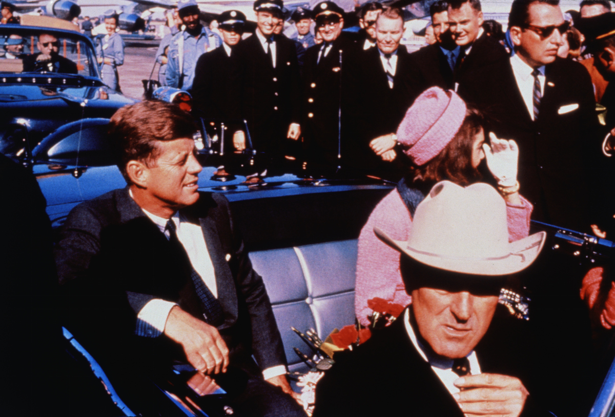 Texas Governor John Connally adjusts his tie (foreground) as President and Mrs. Kennedy, in a pink outfit, settled in rear seats, prepared for motorcade into city from airport in Dallas, Nov. 22, 1963. After a few speaking stops, the President was assassinated in the same car.