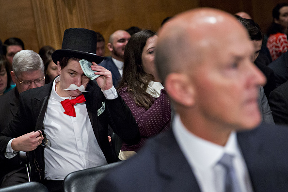 A demonstrator sits in costume behind Richard Smith, former CEO of Equifax, before a Senate Banking Committee hearing in Washington, D.C., on Oct. 4, 2017.