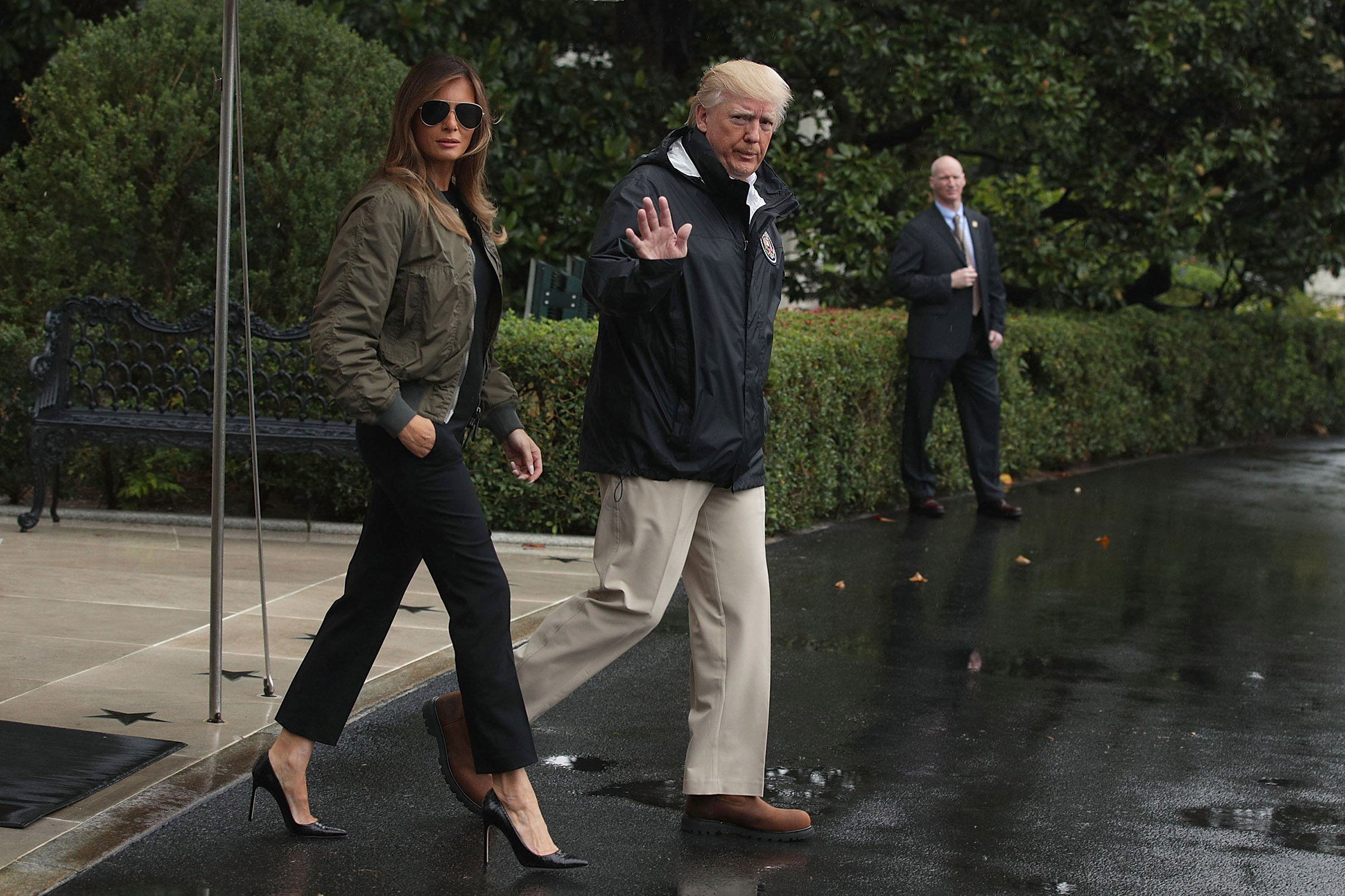 President Donald Trump walks with first lady Melania Trump, wearing a green bomber jacket, black pants and t-shirt and Manolo Blahnik stilettos, on way to Texas to observe the Hurricane Harvey relief efforts, Aug. 29, 2017.