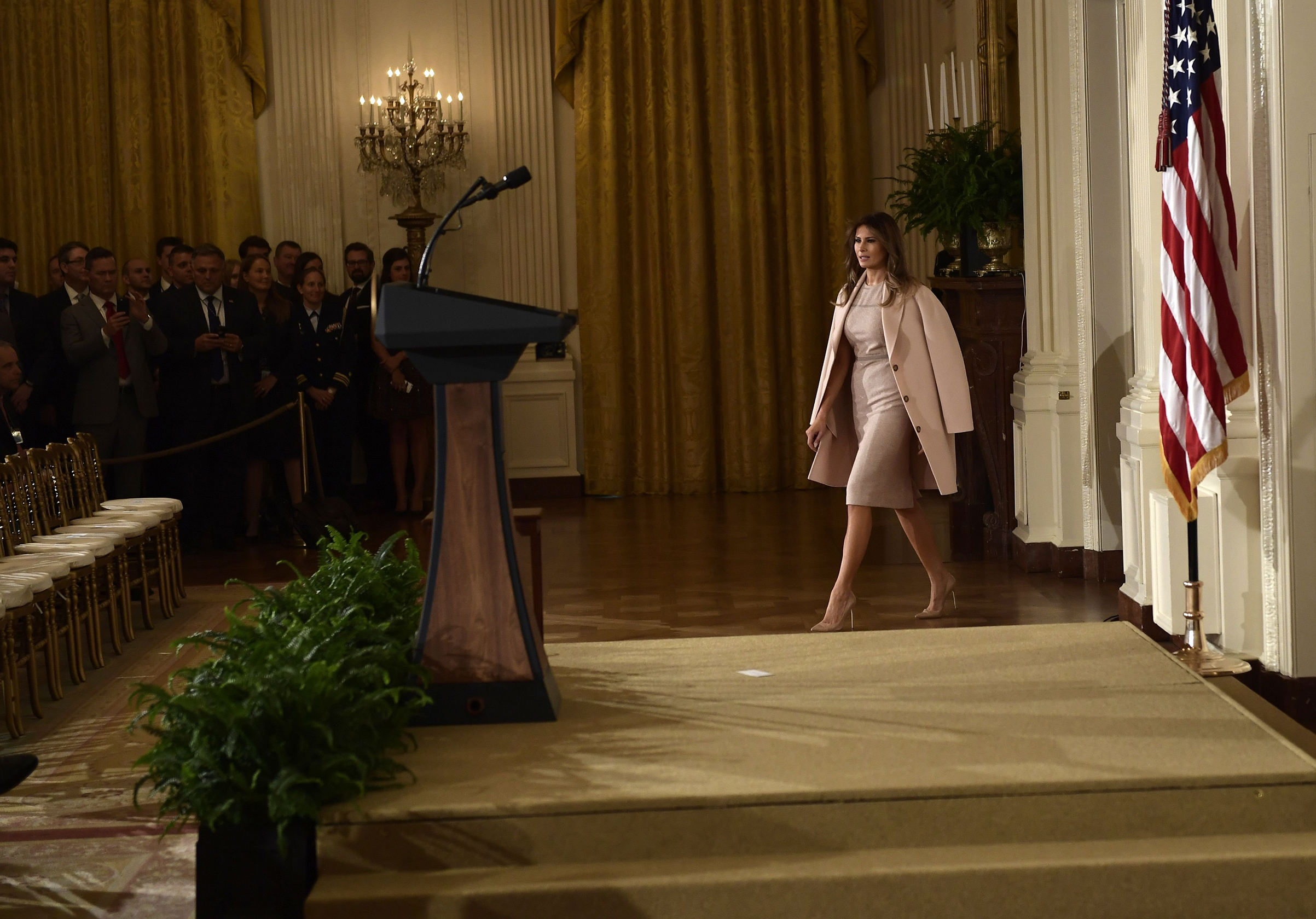 First lady Melania Trump wearing a beige dress by Agnona and a pale pink coat from Acne Studios, arrives for an event Oct. 12, 2017 at the White House in Washington, D.C.