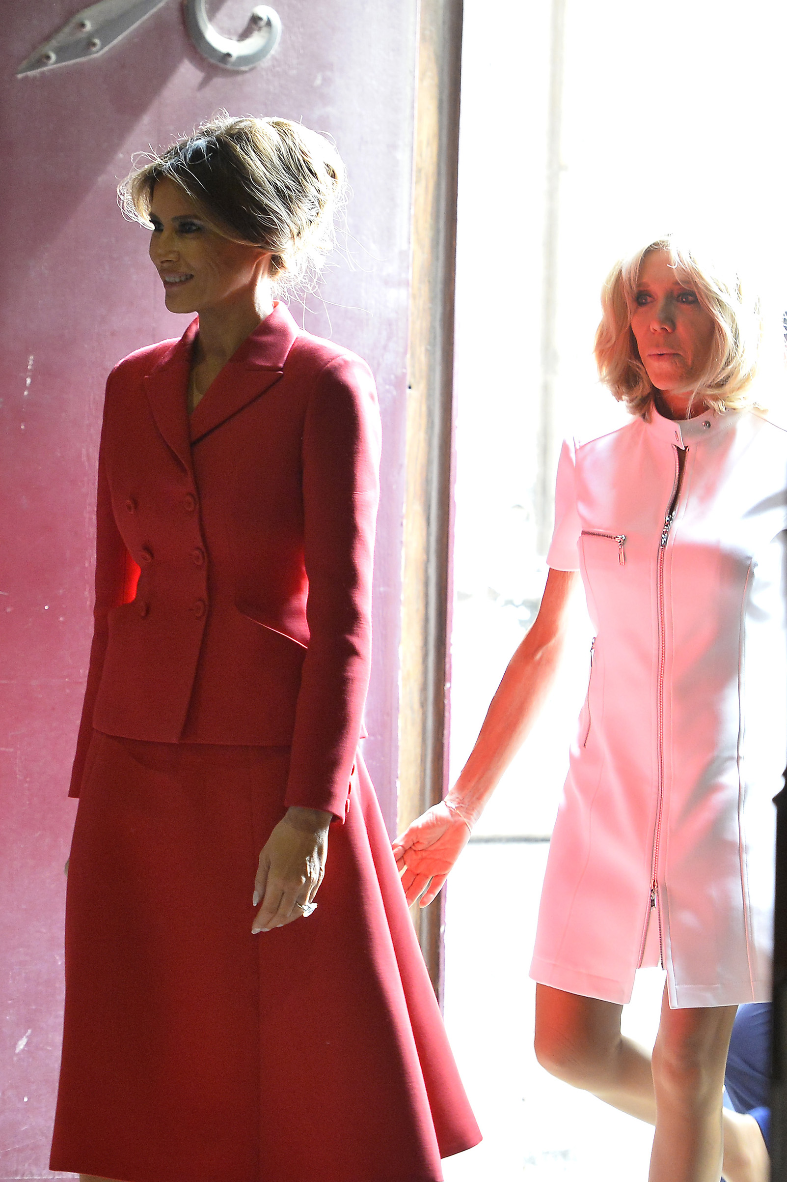 First lady Melania Trump  in red Dior skirt suit, and French First Lady Brigitte Macron arrive to visit Notre Dame Cathedrale on July 13, 2017 in Paris, France.