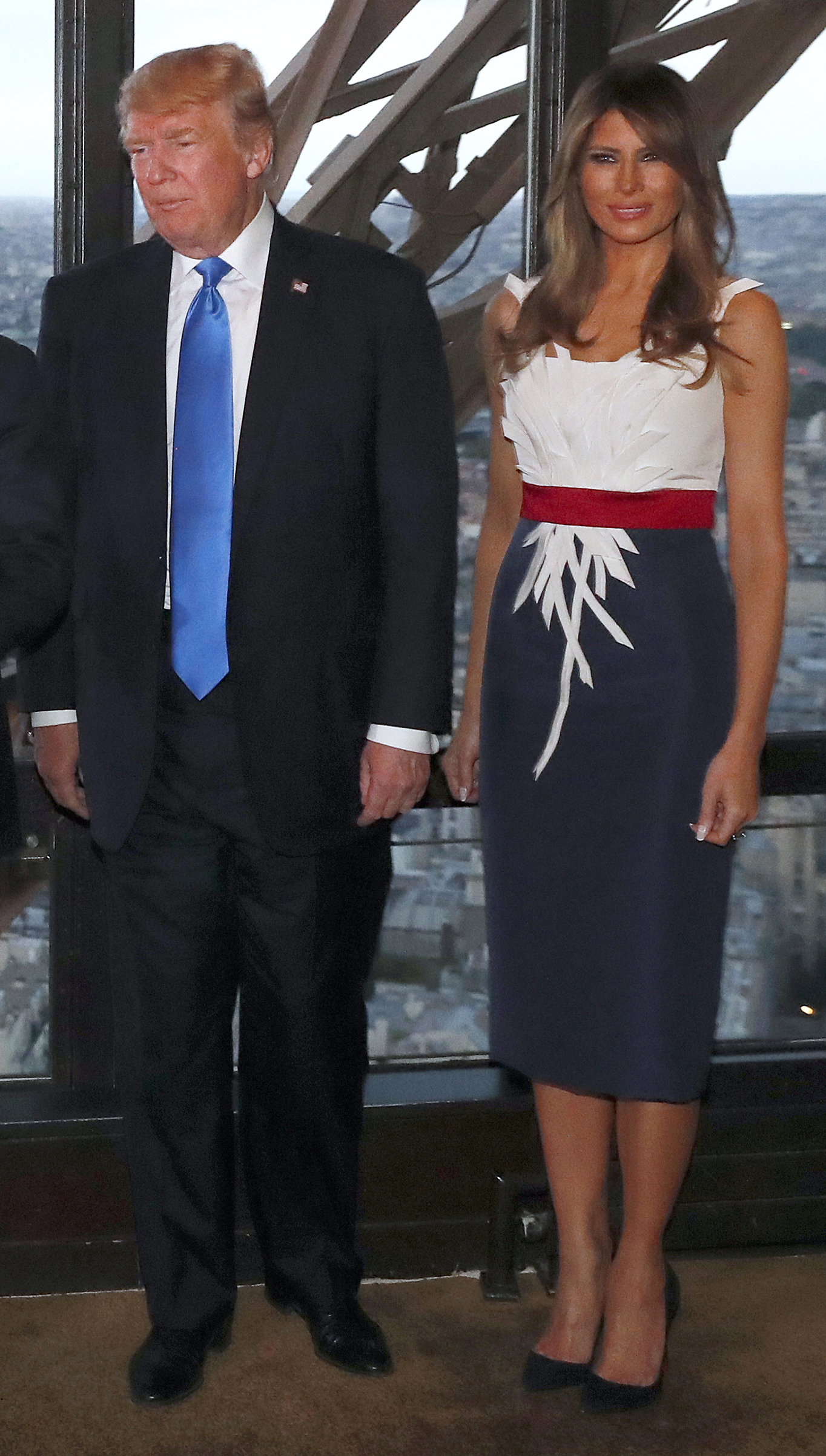 President Donald Trump (L) and first lady Melania Trump (R) in a dress created by  Hervé Pierre, pose upon their arrival for a dinner with French President and his wife, at Le Jules Verne Restaurant on the Eiffel Tower in Paris, on July 13, 2017.