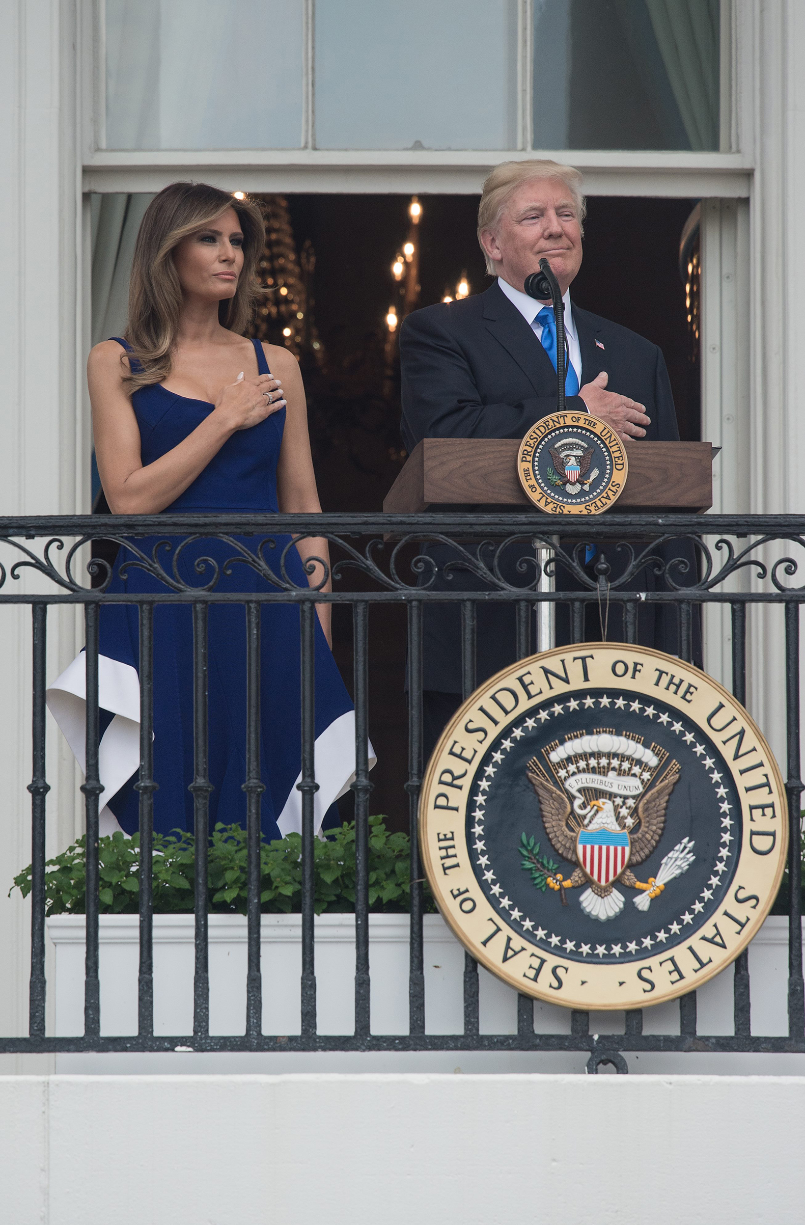 President Donald Trump and first lady Melania Trump,   wearing a blue and white dress by designer Esteban Cortázar, listen to the national anthem during the military families picnic at the White House in Washington, D.C, on July 4, 2017.