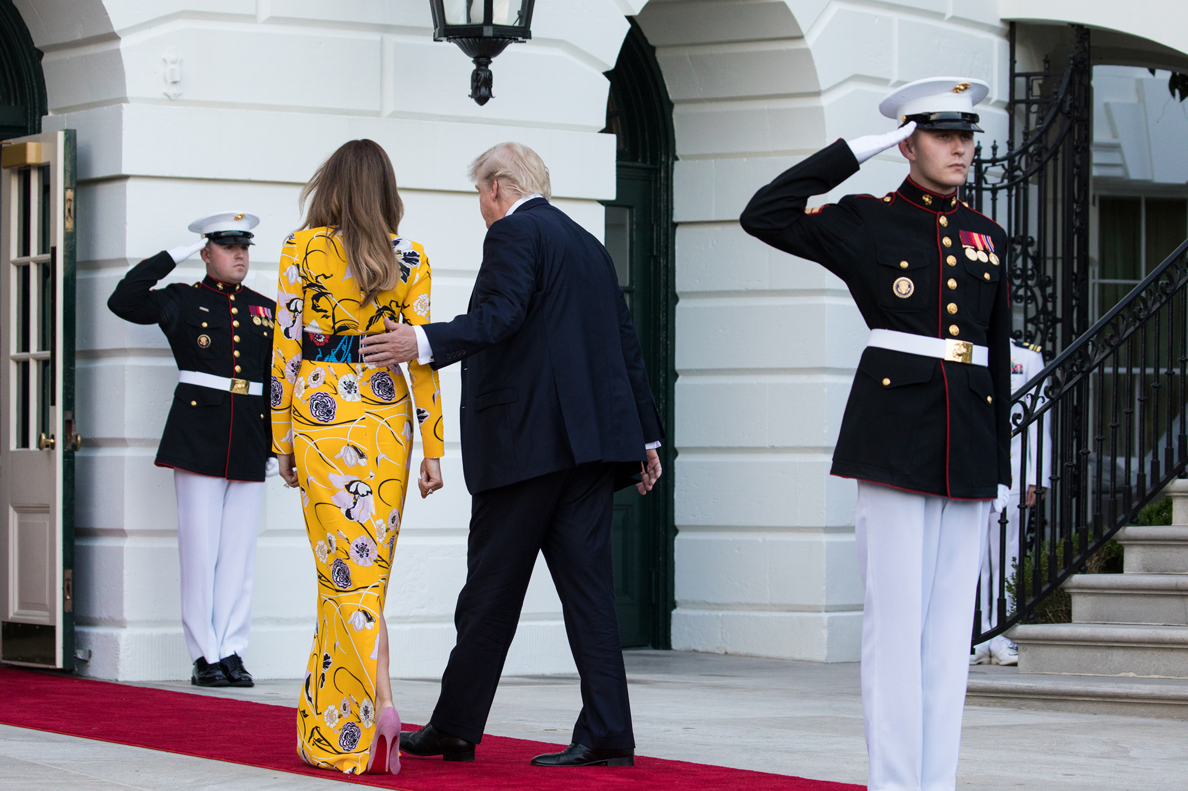 First lady Melania Trump wearing a yellow Pucci dress and President Donald Trump head back in to the White House, after the departure of Prime Minister Narendra Modi of India, June 26, 2017.