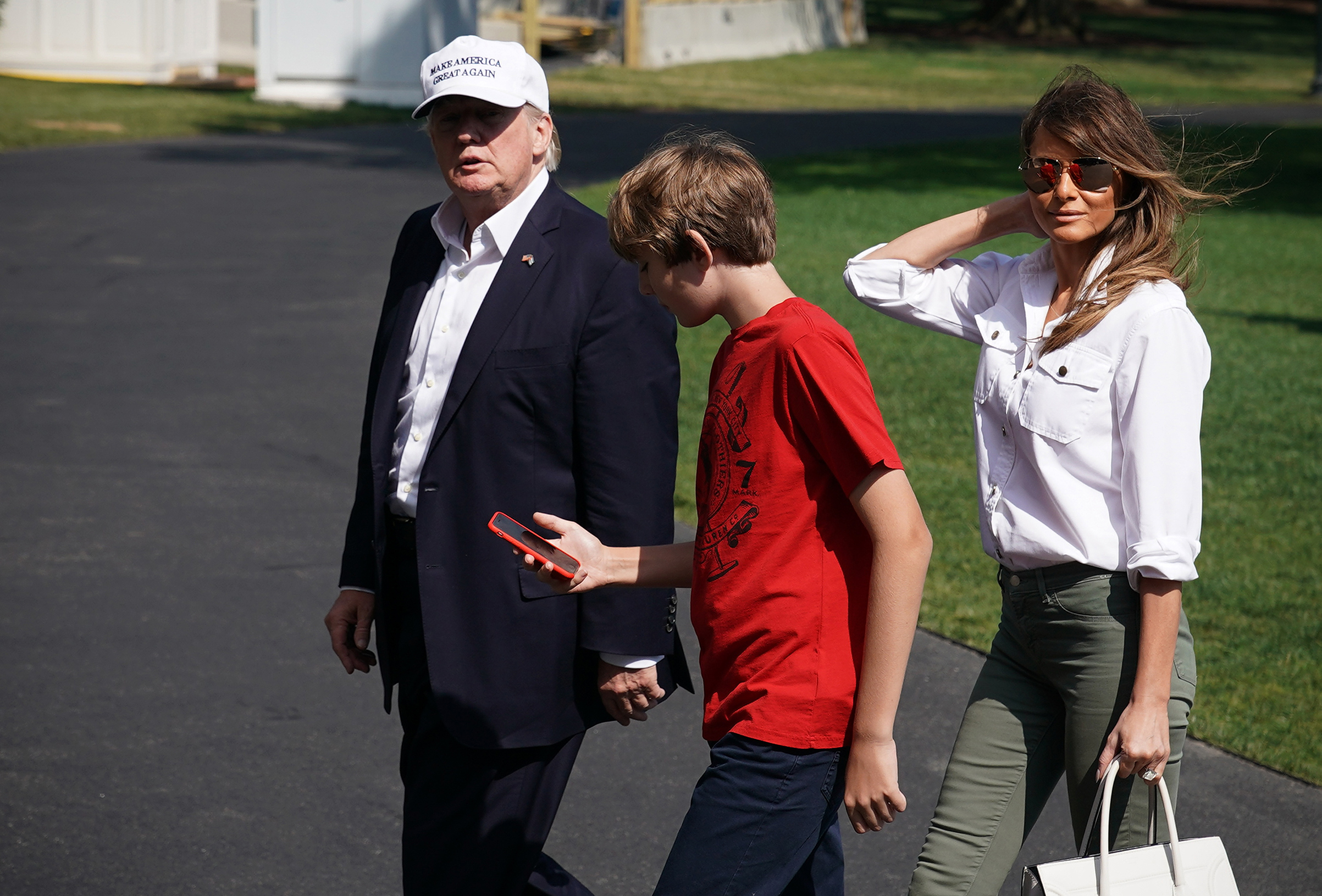President Donald Trump, first lady Melania Trump wearing a white button-up top and olive green J Brand pants, and their son Barron walk across the South Lawn upon return to the White House on June 18, 2017.