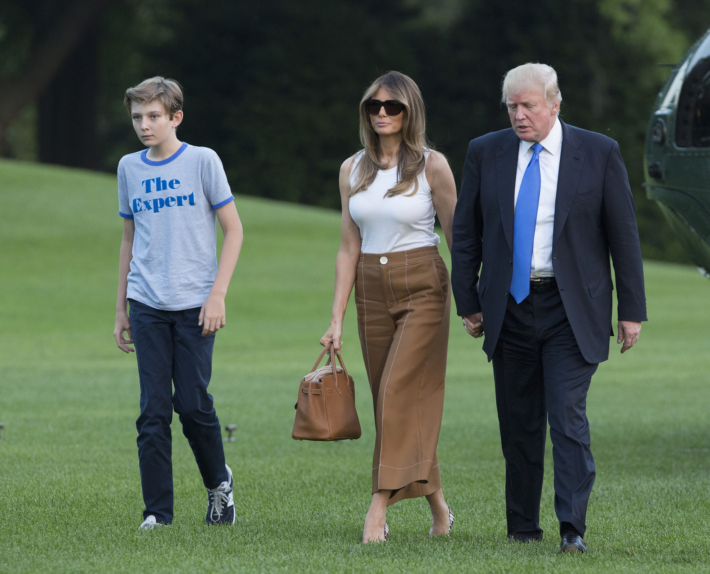 President Donald Trump, first lady Melania Trump wearing tan wide-legged pants by Bally with a white Dolce & Gabbana tank, and their son Barron Trump arrive at the White House June 11, 2017.