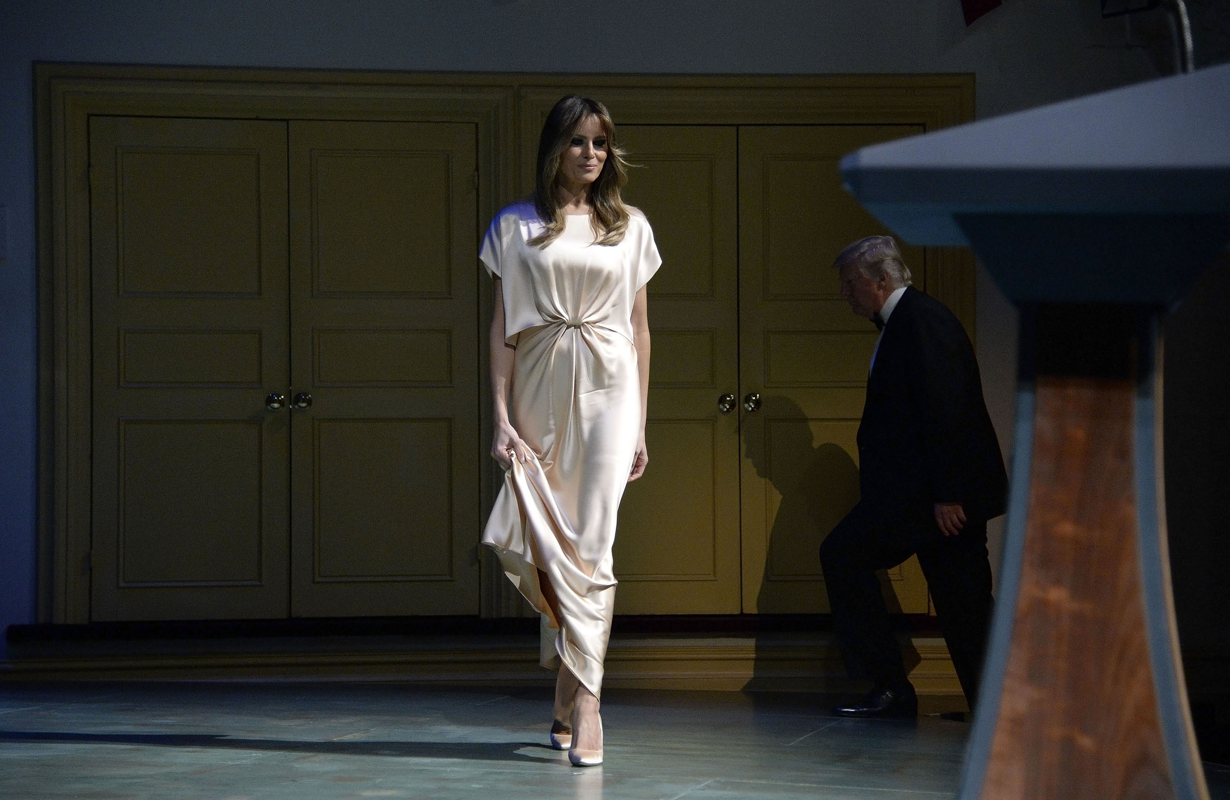 President Donald Trump and First Lady Melania Trump wearing a nude satin gown by Filipino designer Monique Lhuillier,  walk on stage during the annual gala at the Ford's Theatre to honor President Abraham Lincoln's legacy , on June 4, 2017.