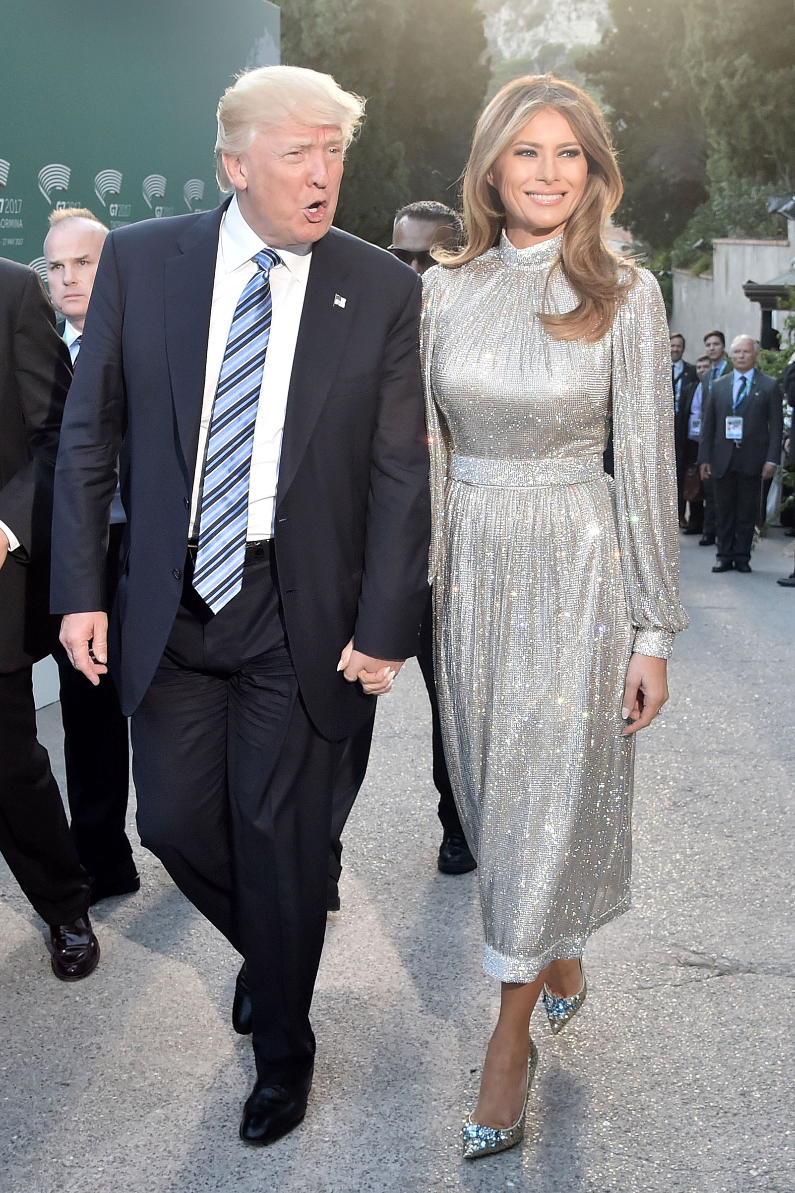 President Donald Trump and first lady Melania Trump wearing wearing a Dolce & Gabbana's glittering dress and silver shoes, hold hands as they arrive for a concert of La Scala Philharmonic Orchestra at the ancient Greek Theatre of Taormina during the Heads of State and of Government G7 summit, on May 26, 2017 in Sicily, Italy.
