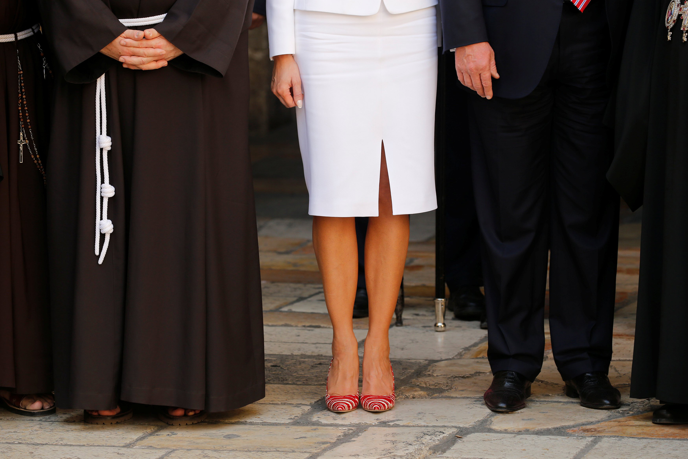 First lady Melania Trump wearing white Michael Kors Collection suit and Manolo Blahnik's red and white striped stilettos, stands next to members of the Christian clergy during her visit with her husband U.S. President Donald Trump to the Church of the Holy Sepulchre in Jerusalem's Old City,  May 22, 2017.