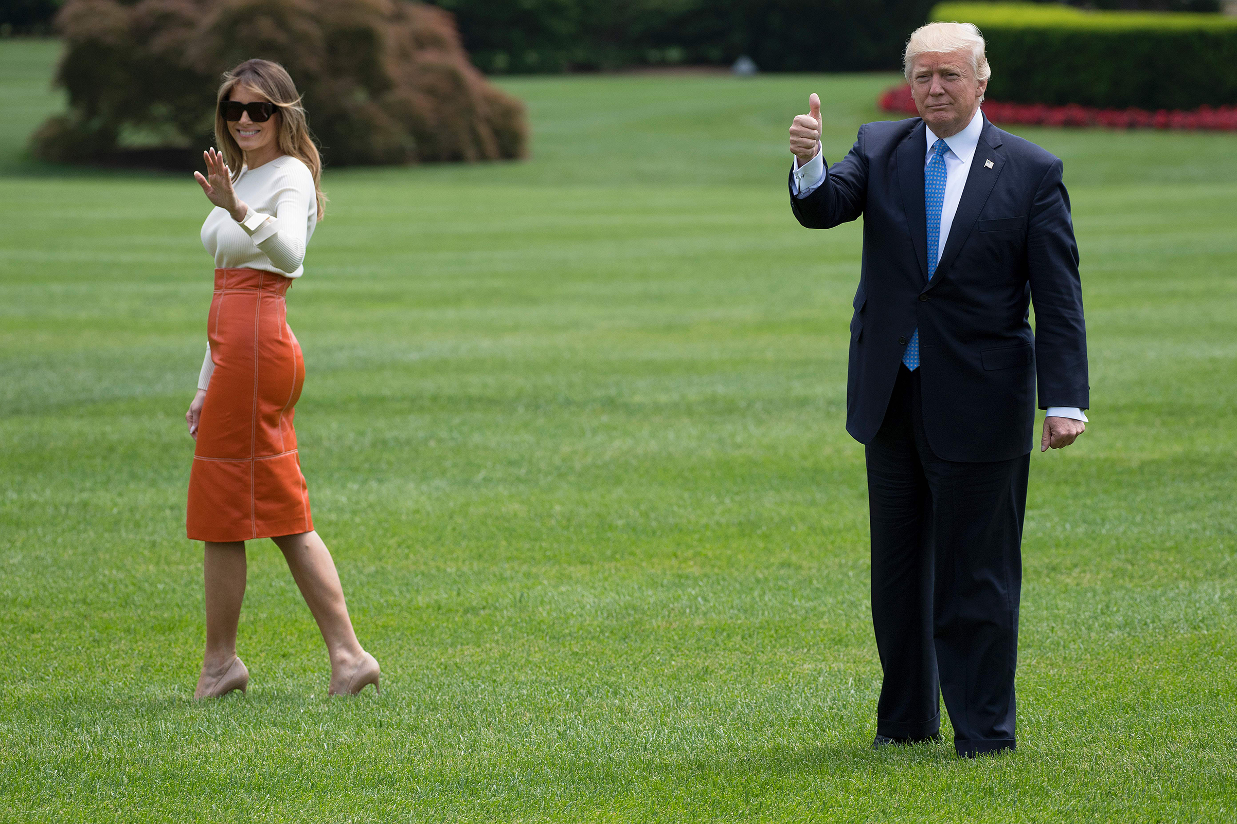 President Donald Trump (R) gives a thumbs up as he and First Lady Melania Trump wearing a Max Mara sweater and Hervé Pierre leather skirt, depart the White House in Washington, DC, May 19, 2017.