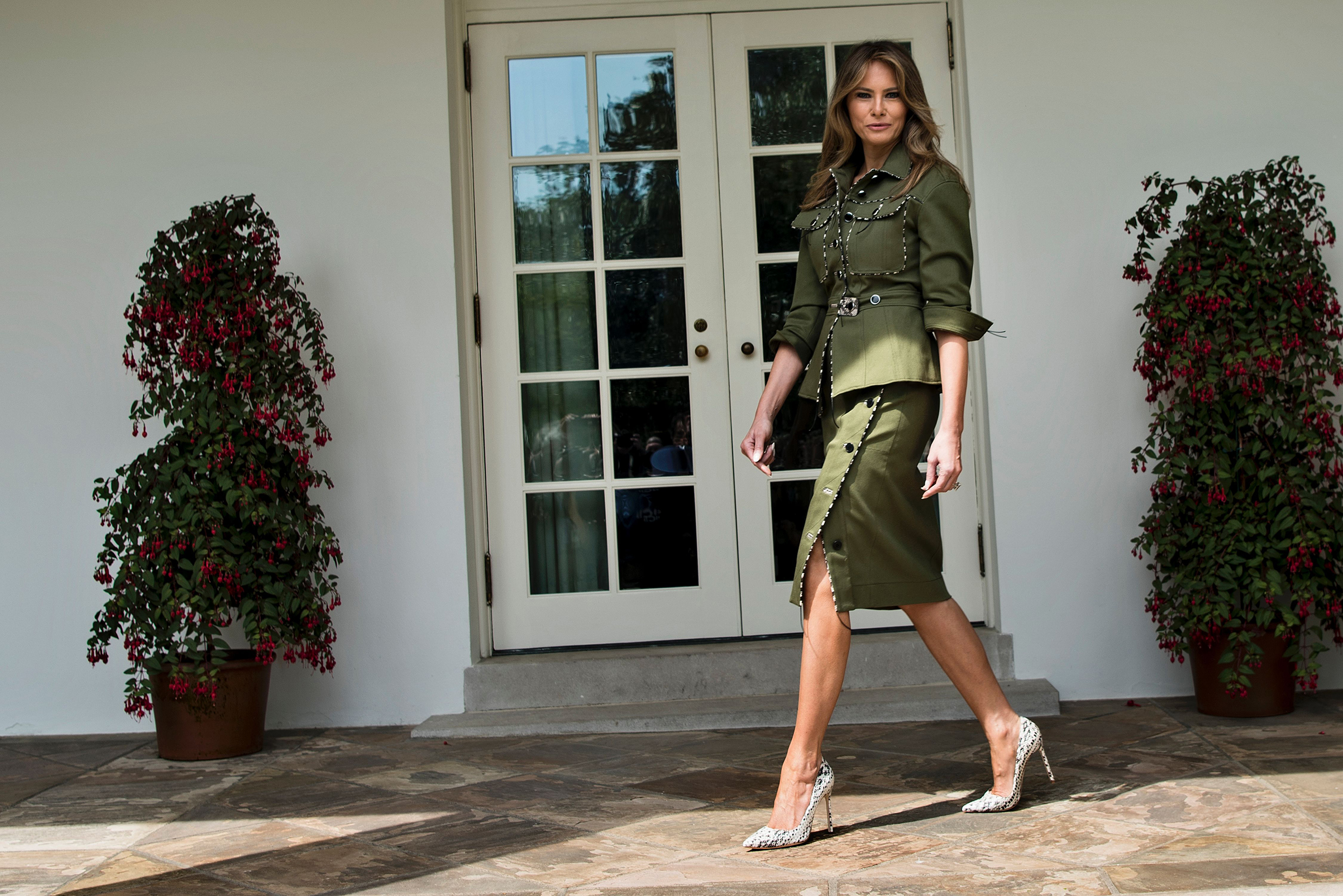 First lady Melania Trump wearing a khaki green, military-look suit by Altuzarra walks past the West Wing of the White House April 27, 2017.
