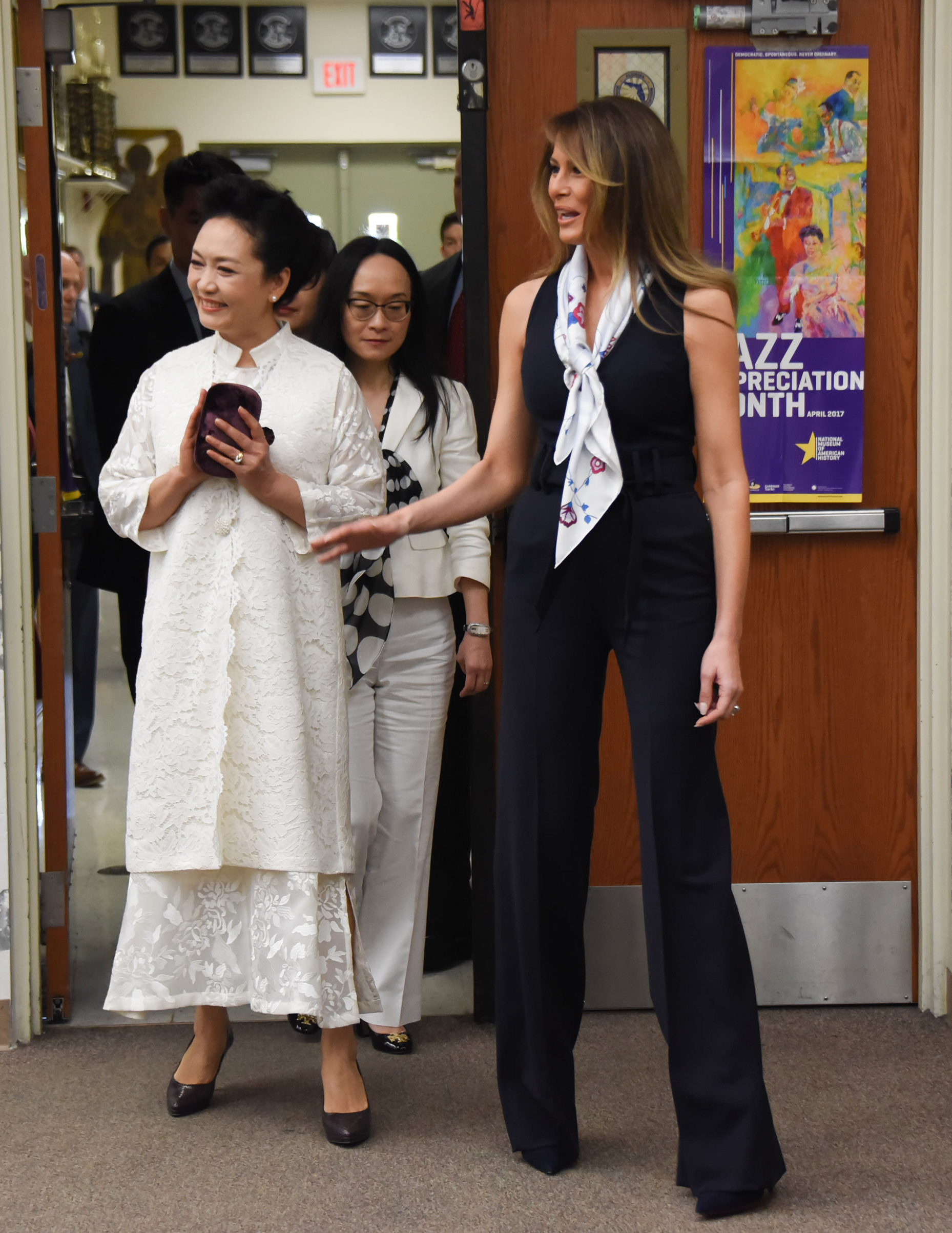 First lady Melania Trump  wearing black belted jumpsuit with a floral scarf and People's Republic of China First Lady Peng Liyuan visit the Bak Middle School of the Arts on April 7, 2017 in West Palm Beach, Florida.
