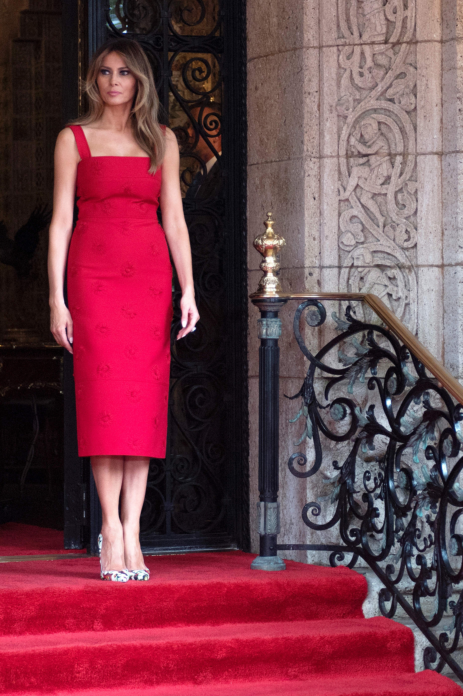 First lady Melania Trump wears a sleeveless red daisy-appliqué crepe midi dress by Valentino, awaits the arrival of Chinese President Xi Jinping and his wife Peng Liyuan at the Mar-a-Lago estate in West Palm Beach, Fla., on April 6, 2017.