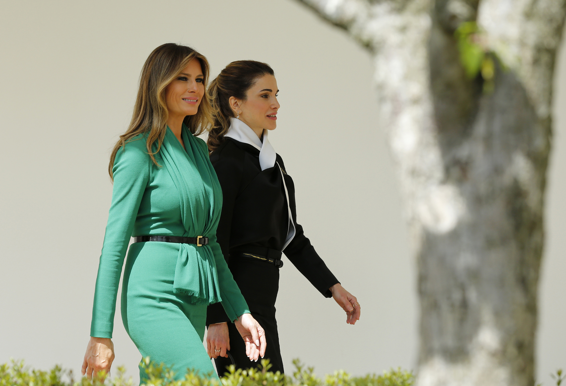 First lady Melania Trump (L) wearing emerald green dress by Hervé Pierre walks down the White House colonnade with Jordan's Queen Rania after U.S. President Donald Trump and Jordan's King Abdullah II held a joint news conference in the Rose Garden at the White House in Washington, D.C., April 5, 2017.