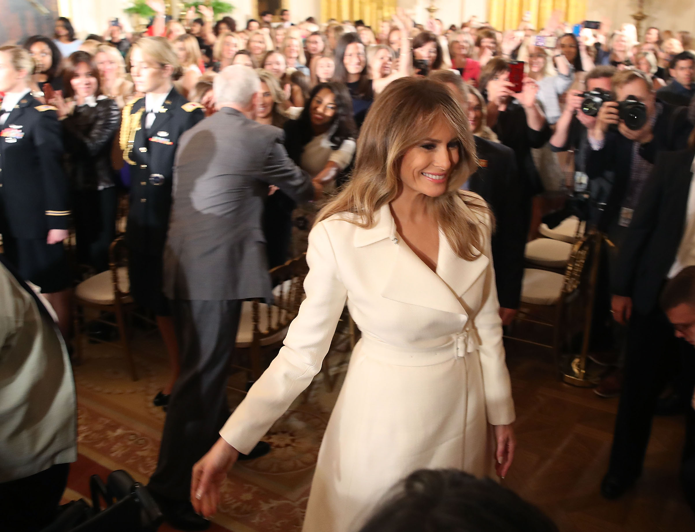 First lady Melania Trump  wearing a white coat dress from The Row, walks away after attending and event celebrating Women's History Month, in the East Room at the White House March 29, 2017 in Washington, D.C.