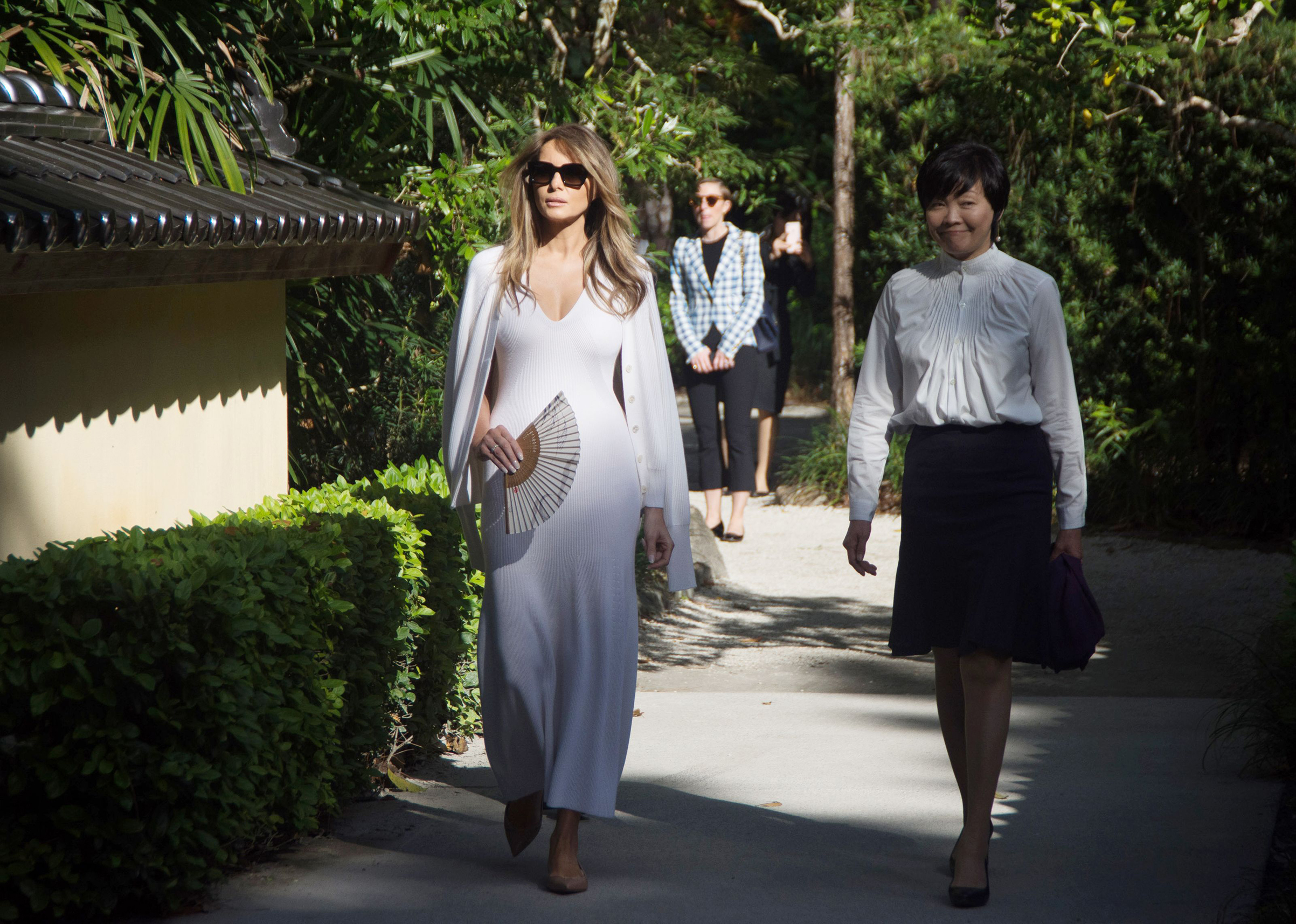 First Lady Melania Trump wearing a sleeveless white cashmere knitted long dress  by Calvin Klein, and Akie Abe, wife of Japanese Prime Minister Shinzo Abe, tour Morikami Museum and Japanese Gardens in Delray Beach, Fla., on Feb. 11, 2017.