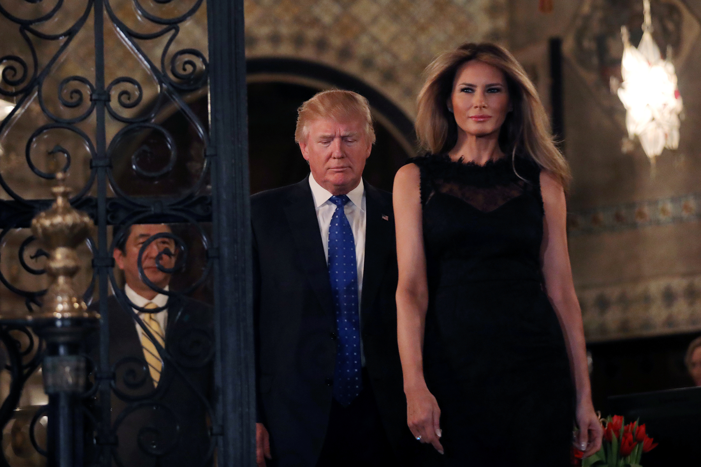 President Donald Trump with first lady Melania wearing a sleeveless black dress with a low-dipping back and a layer of lace on top, walk to pose for a photograph with Japanese Prime Minister Shinzo Abe before attending dinner at Mar-a-Lago Club in Palm Beach, Fla., Feb. 11, 2017.