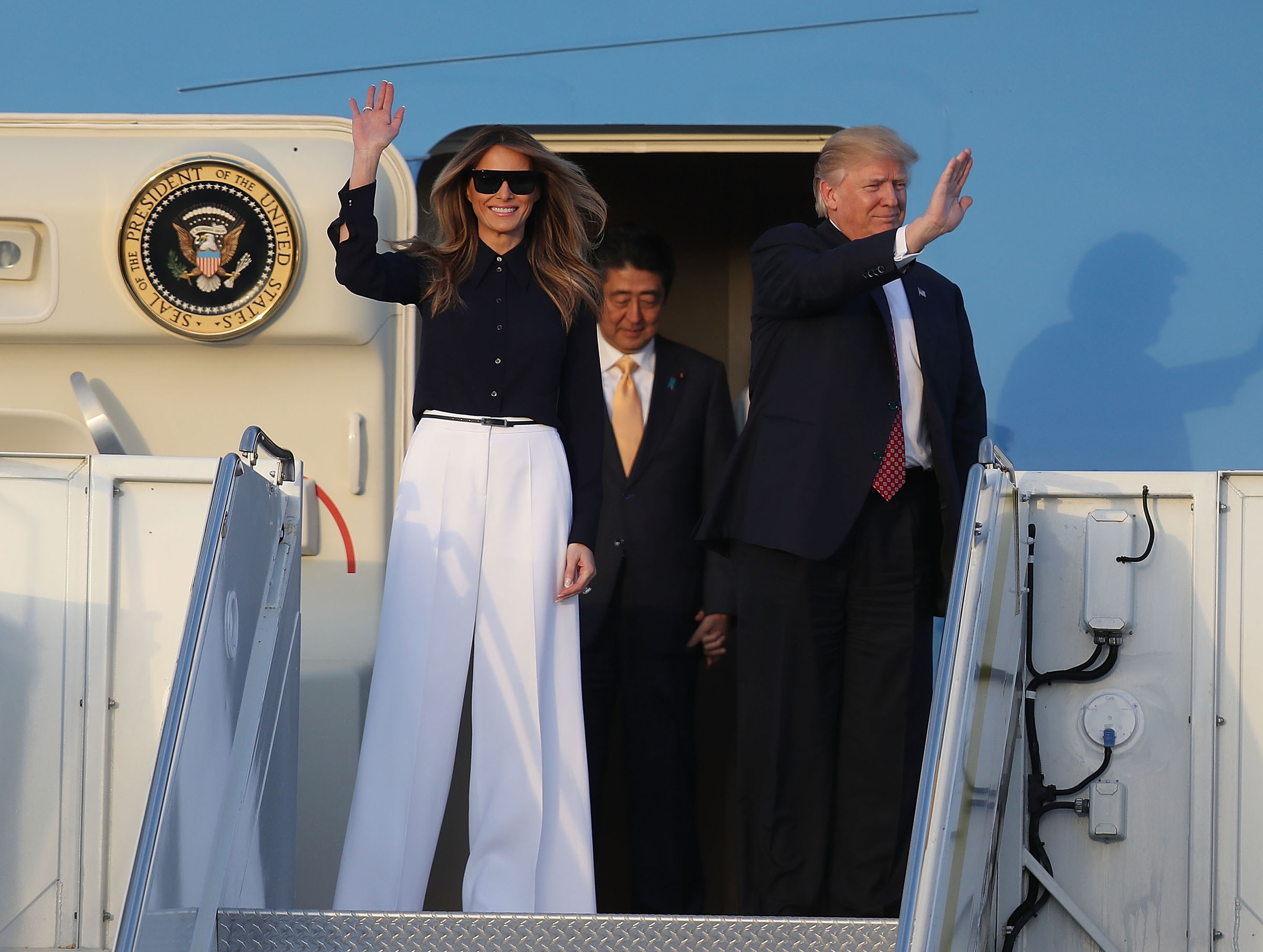 President Donald Trump and first lady Melania Trump , wearing black blouse and white wide-legged pants, arrive with Japanese Prime Minister Shinzo Abe on Air Force One at the Palm Beach International Airport Feb. 10, 2017 in West Palm Beach, Fla.