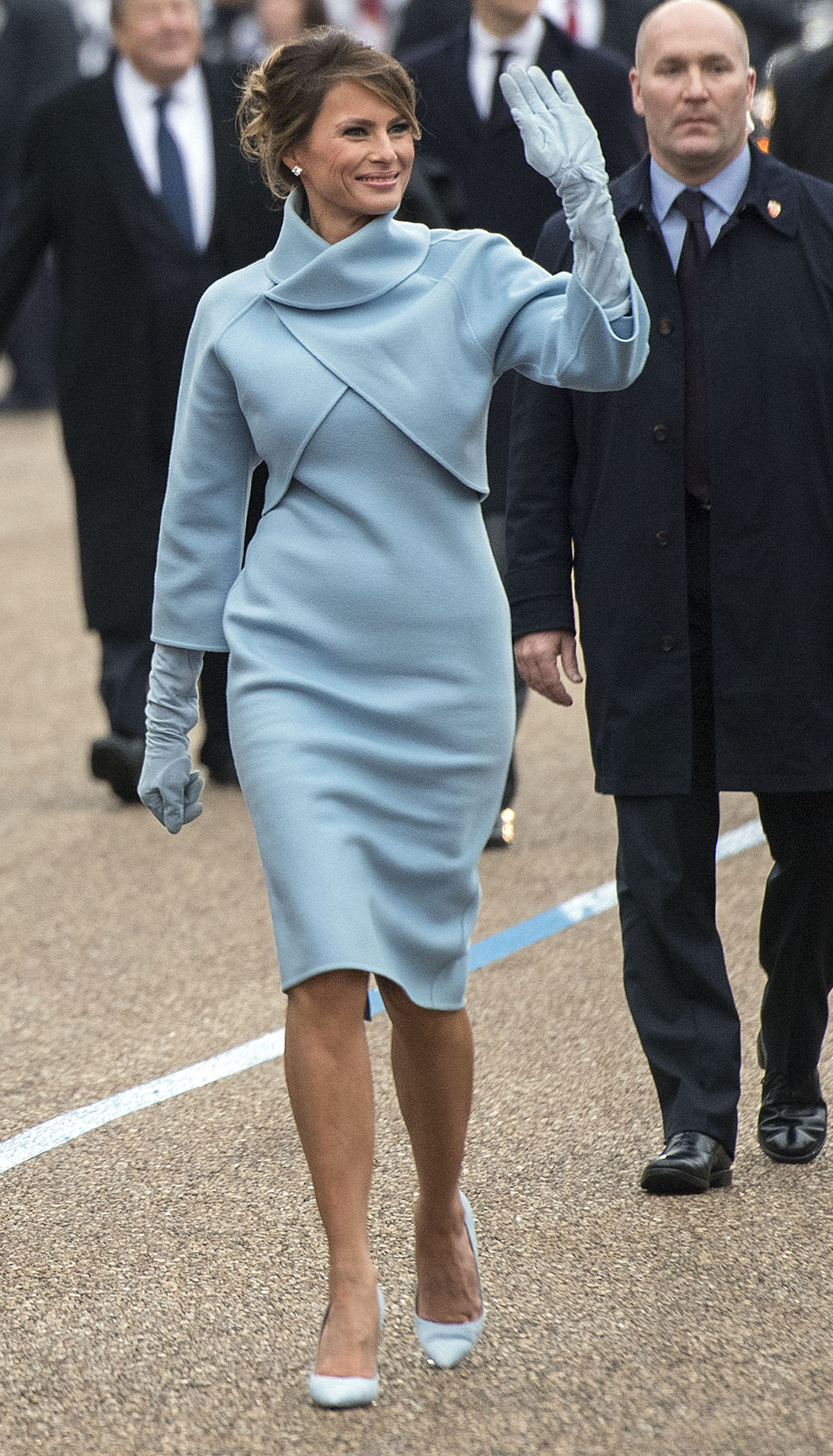 First lady Melania Trump wearing a powder blue cashmere skirt suit by Ralph Lauren Collection,  waves to supporters in the inaugural parade on Jan. 20, 2017 in Washington, DC.