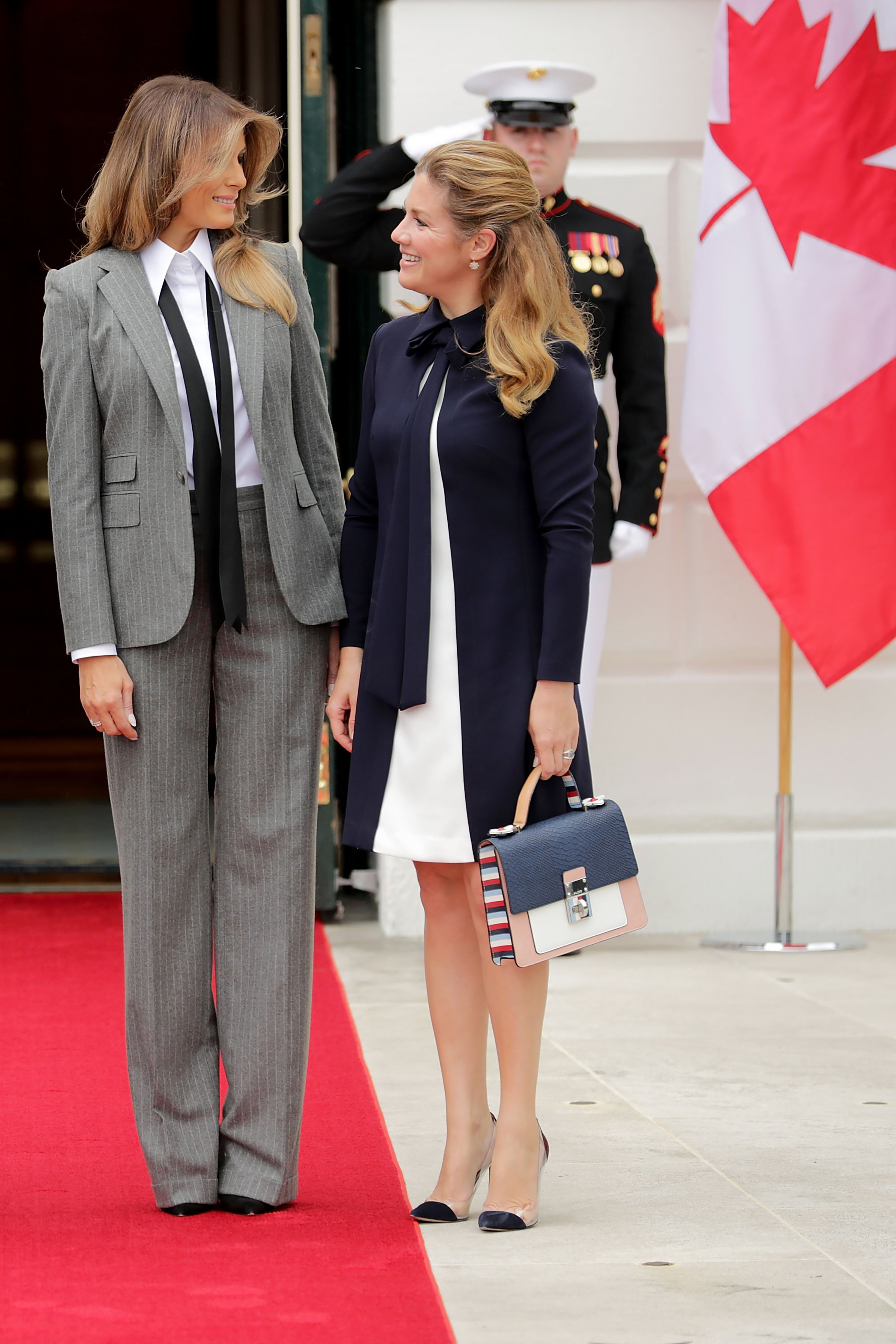 First lady Melania Trump (L) wearing grey pinstriped Ralph Lauren Collection suit, and Sophie Gregoire Trudeau pose for photographs at the White House Oct. 11, 2017 in Washington, D.C.
