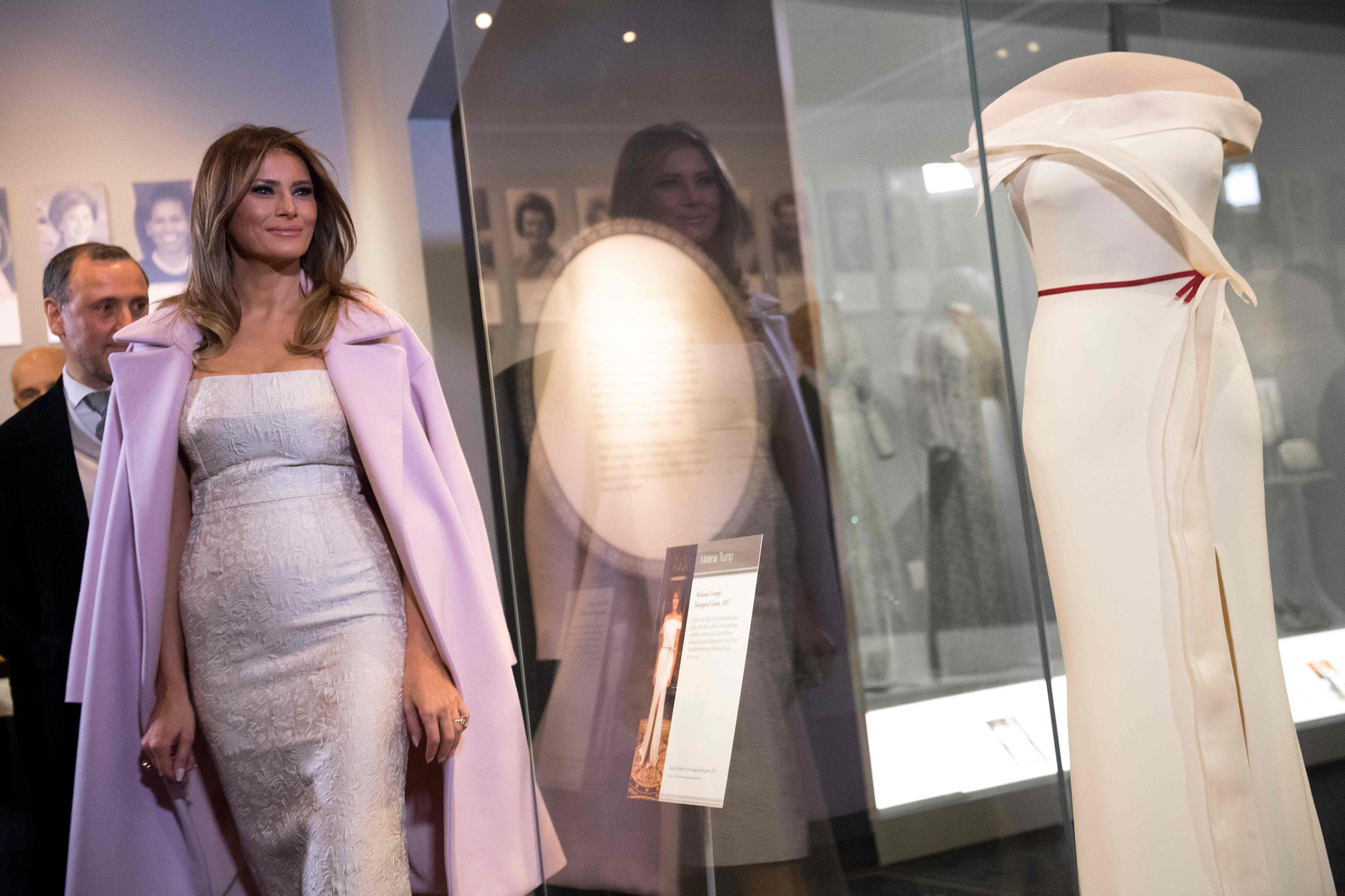 First lady Melania Trump wearing an ivory Dolce & Gabbana dress stands next to Hervé Pierre and his gown, she wore to the 2017 inaugural balls as she donates the dress to the Smithsonian's First Ladies Collection at the Smithsonian National Museum of American History in Washington, D.C., Oct. 20, 2017.