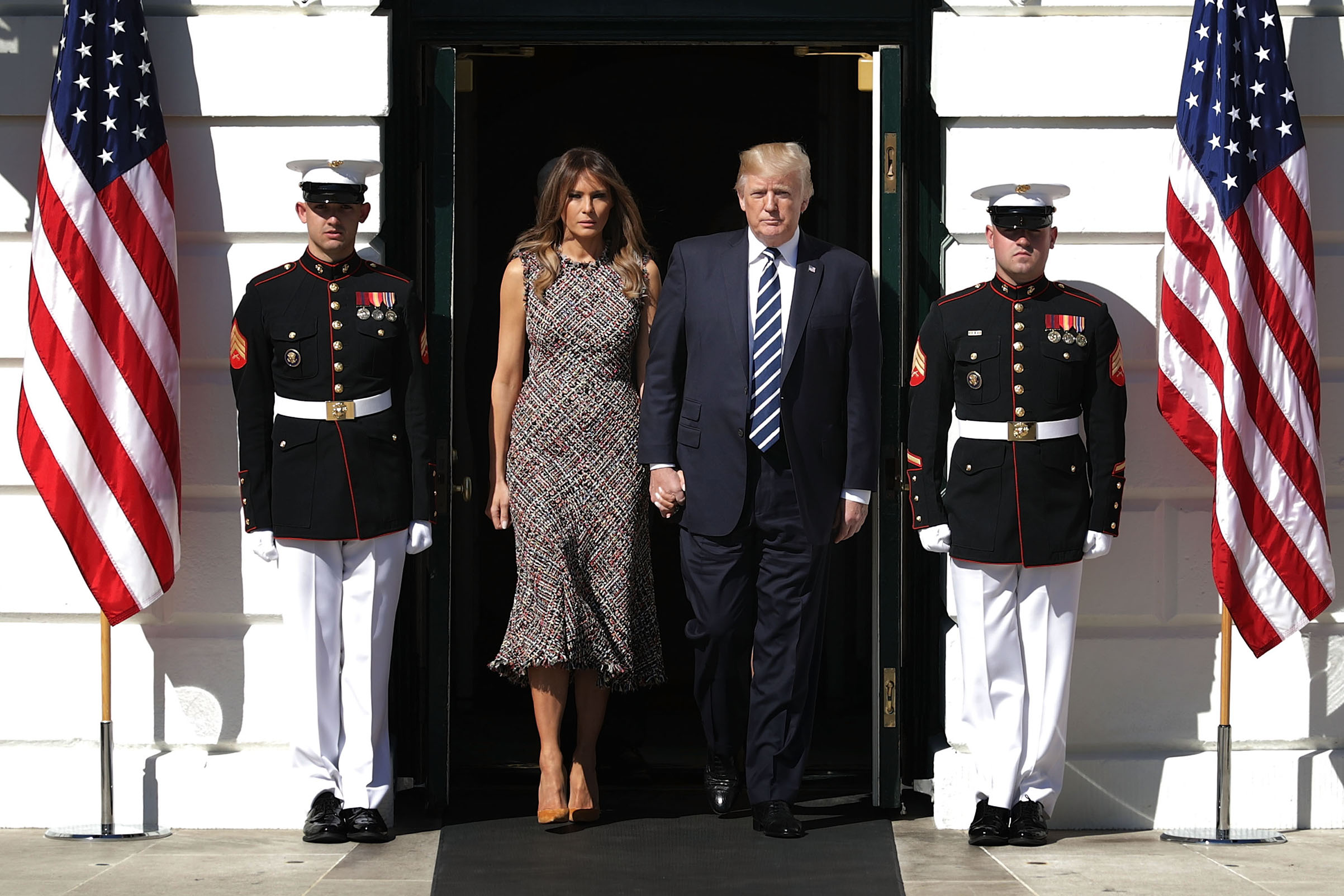 President Donald Trump (R) and first lady Melania Trump wearing a Alexander McQueen tweed midi dress, walk out of the White House before observing a moment of silence on the South Lawn Oct. 2, 2017 in Washington, D.C.