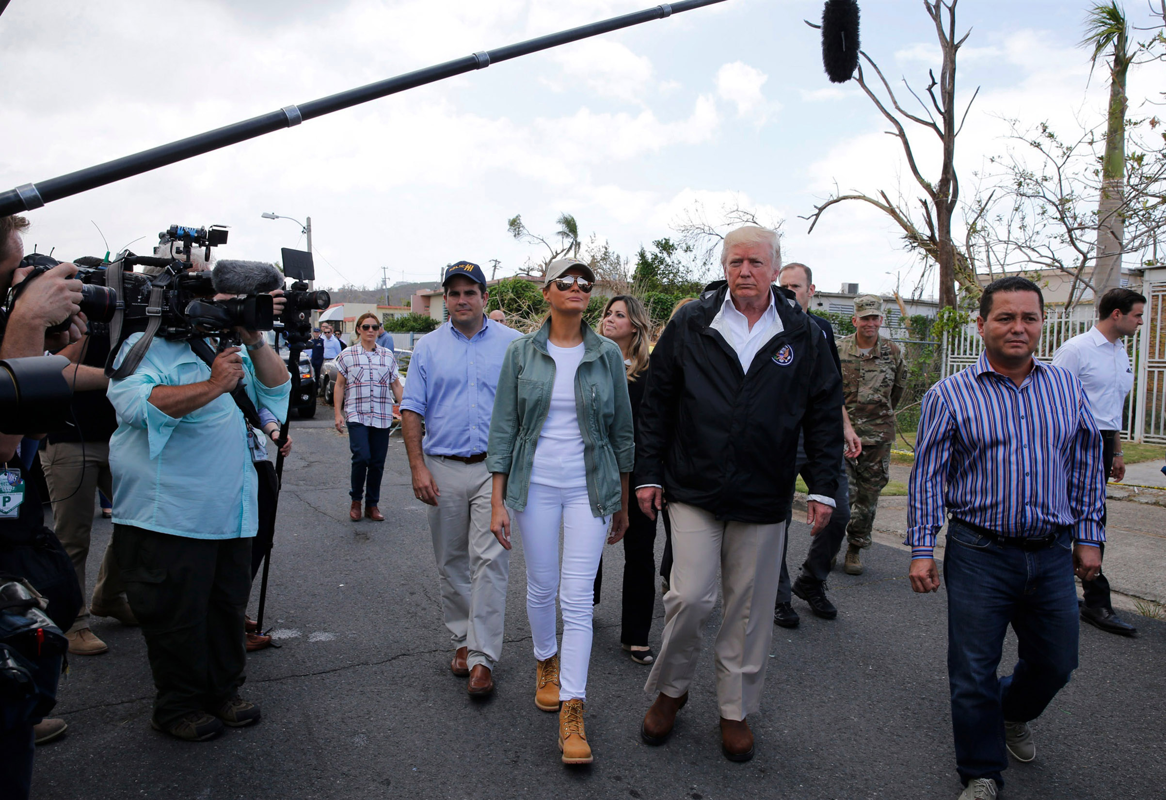 President Donald Trump and first lady Melania walk through a neighborhood damaged by Hurricane Maria in San Juan, Puerto Rico, U.S., Oct. 3, 2017. The first lady wears a baseball cap, a green jacket and Timberland boots.