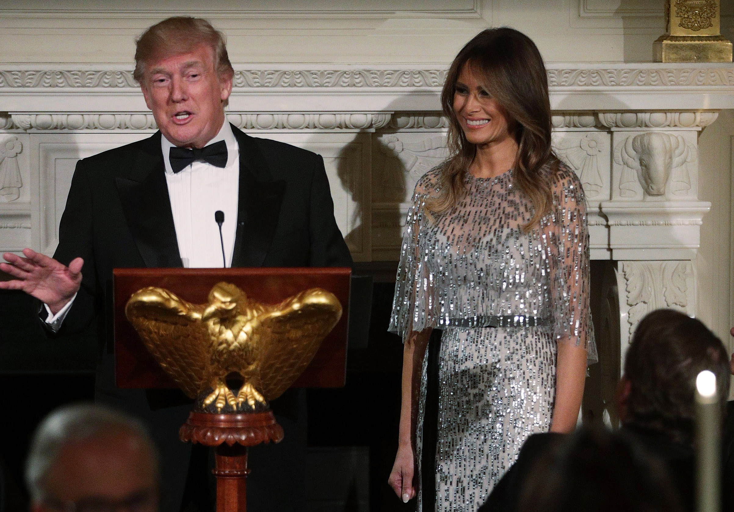 President Donald Trump speaks with  first lady Melania Trump at his side,  wearing a Monique Lhuillier silver dress, during a reception at the State Dining Room of the White House Sept.14, 2017, in Washington, D.C.
