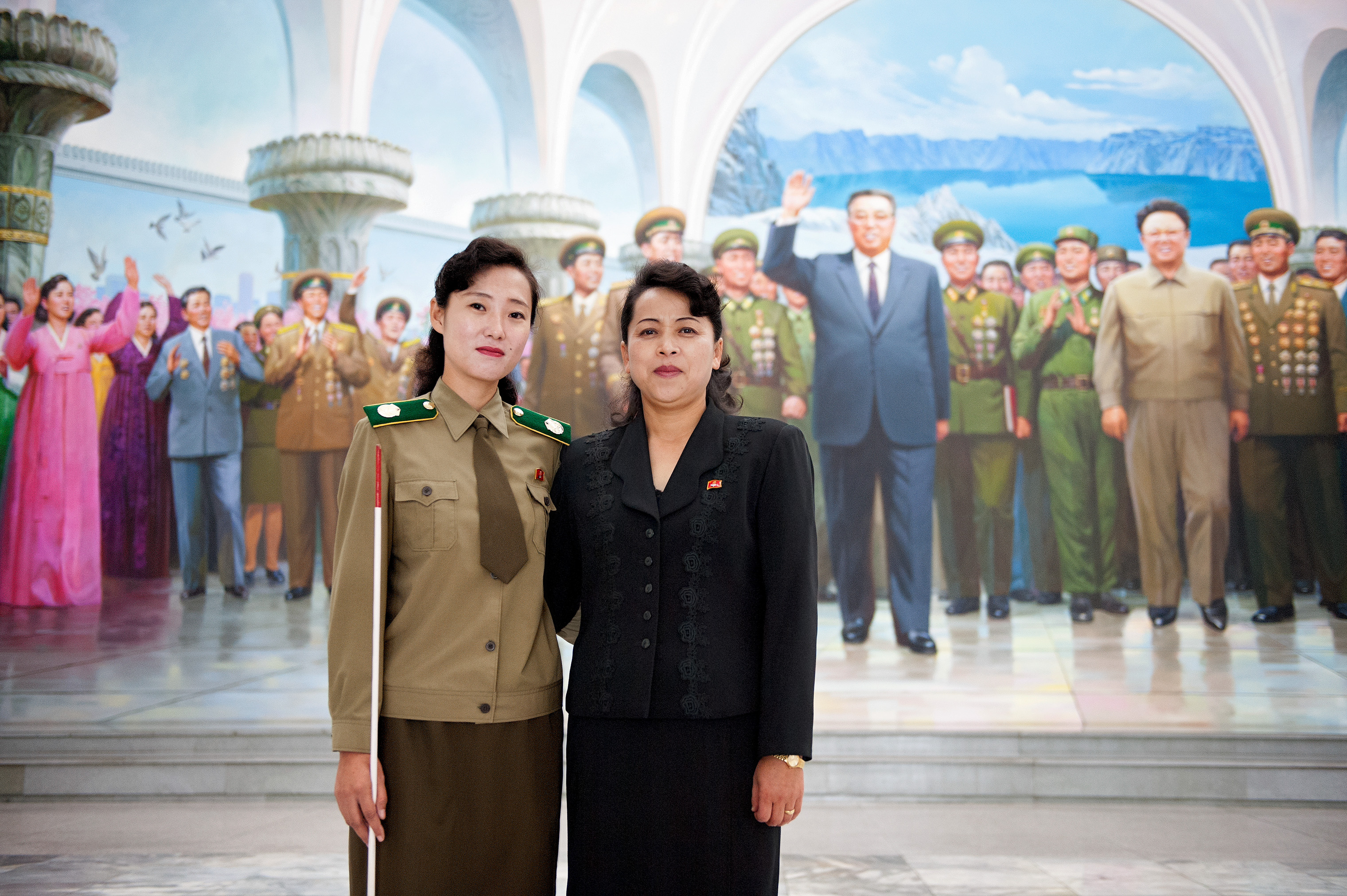 Two local guides pose in front of a mural in Pyongyang.