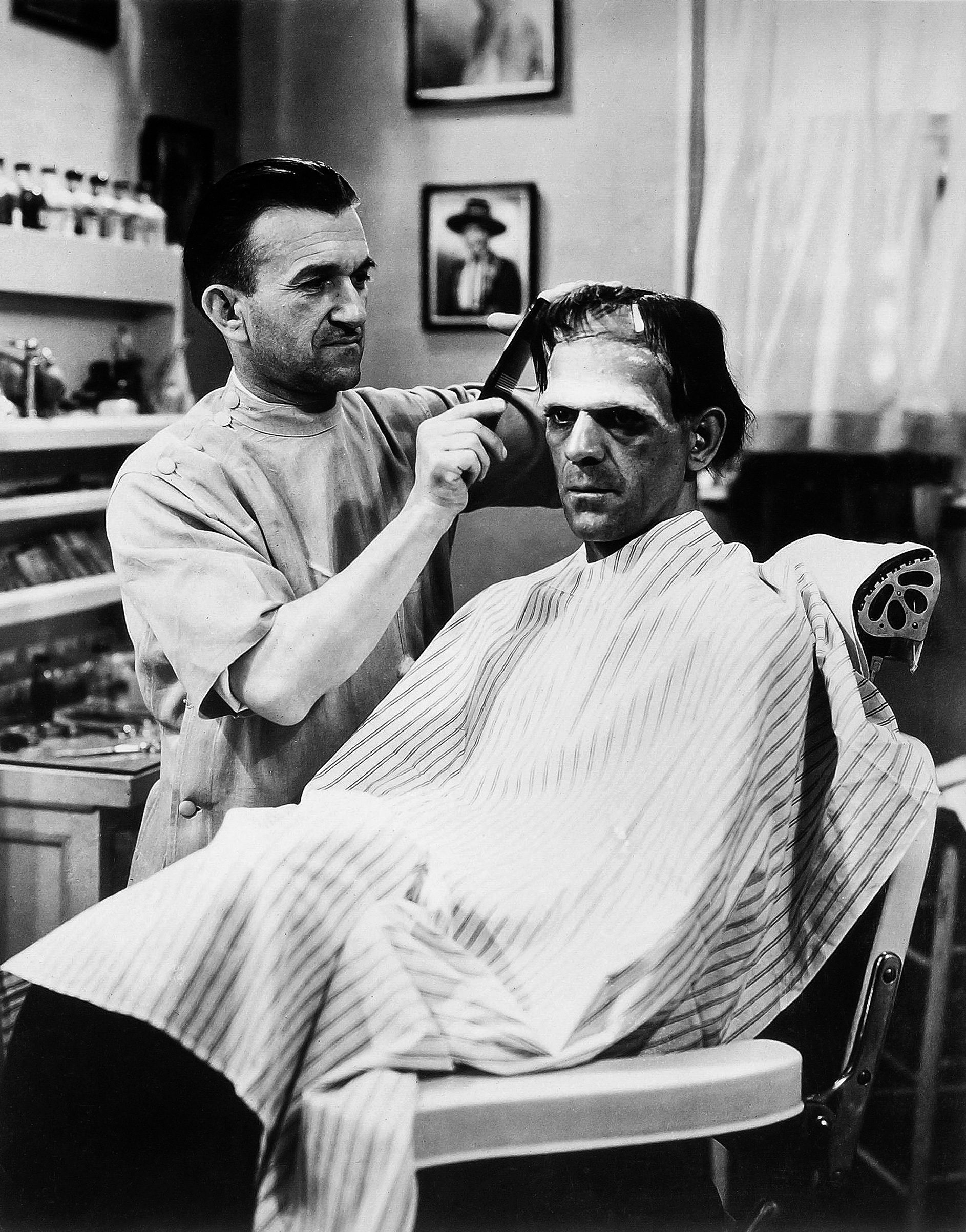 Makeup artist Jack Pierce combs the Monster's wig: according to Boris Karloff, 'it took from four to six hours a day to make me up . . .'  (1931).