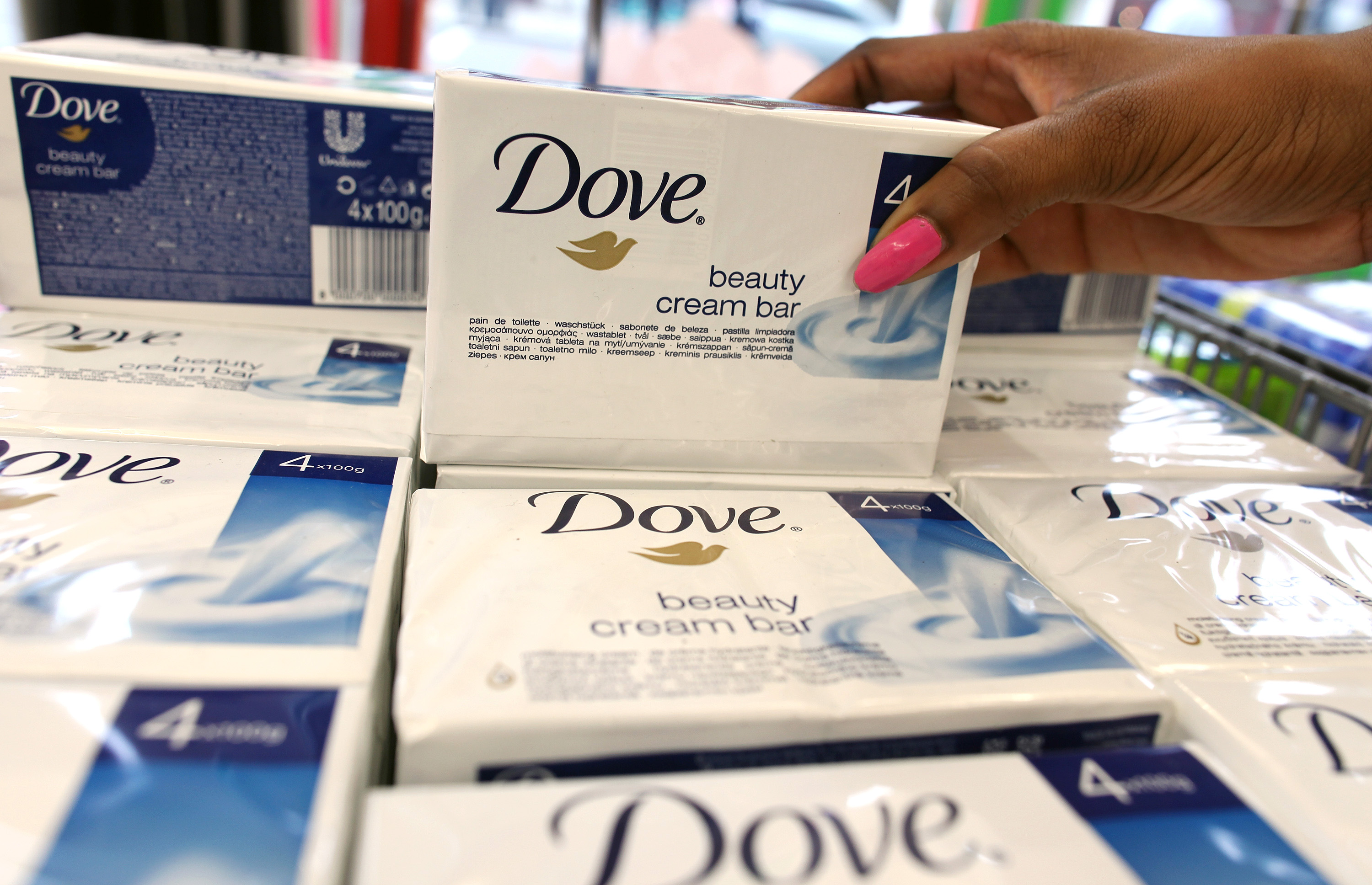 A customer selects a packet of Dove beauty cream, produced by Unilever Plc. from a display at a supermarket in London, on  Nov. 17, 2010.
