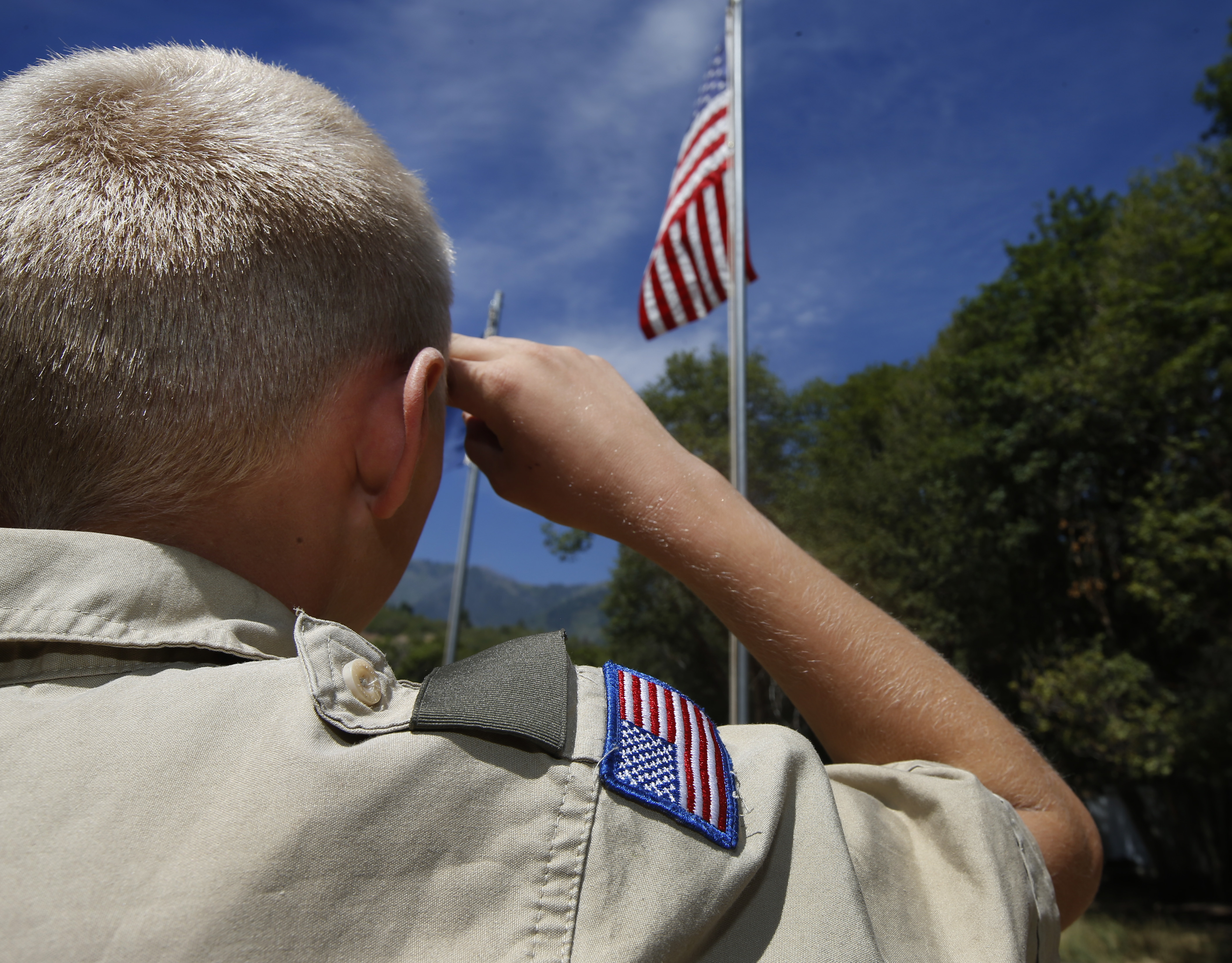 A Boy Scout salutes the American flag at camp Maple Dell on July 31, 2015 outside Payson, Utah.