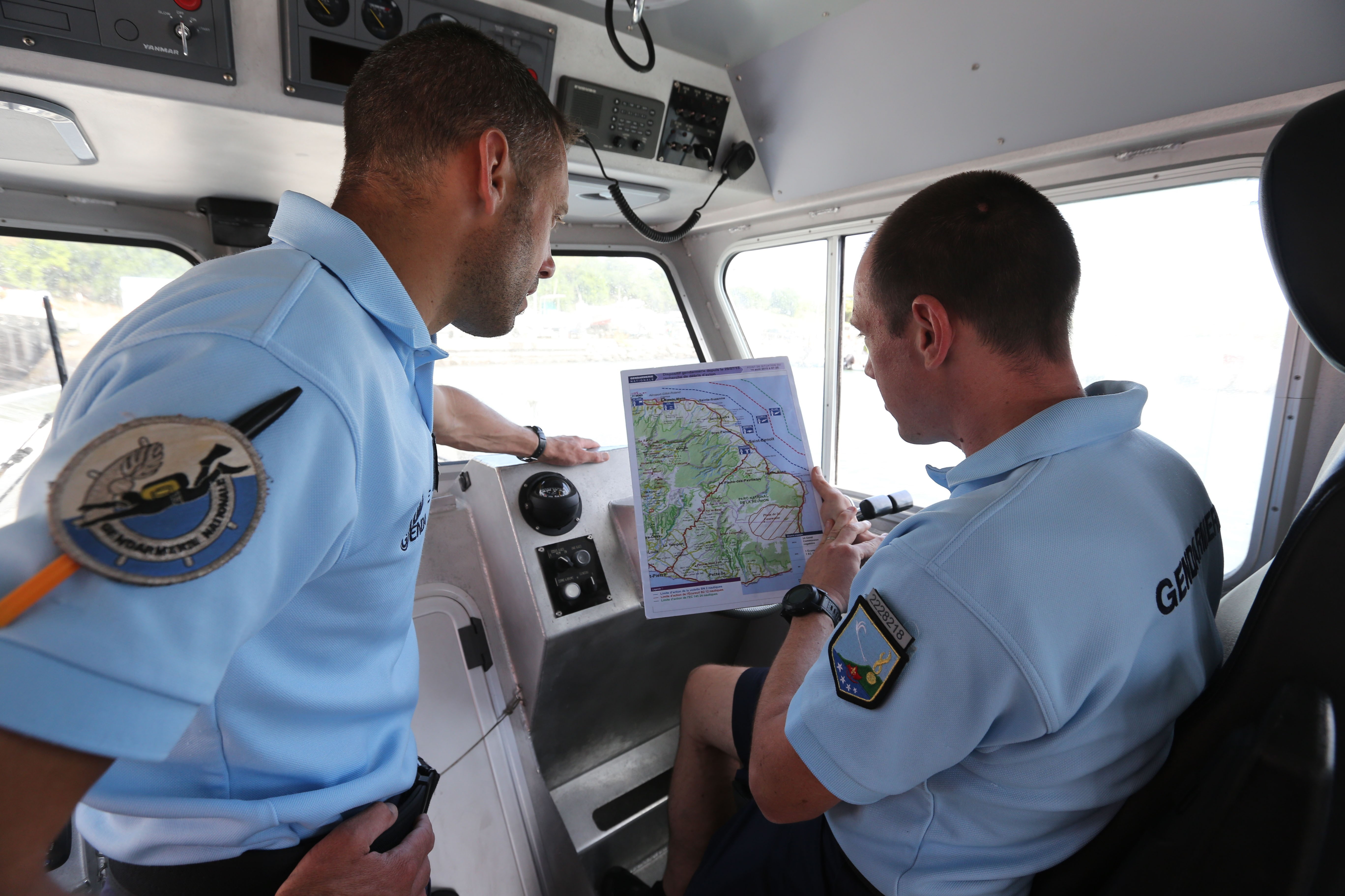 French maritime gendarmes look at a map during the search for wreckage from the missing MH370 plane on the French island of La Reunion on August 14, 2015.