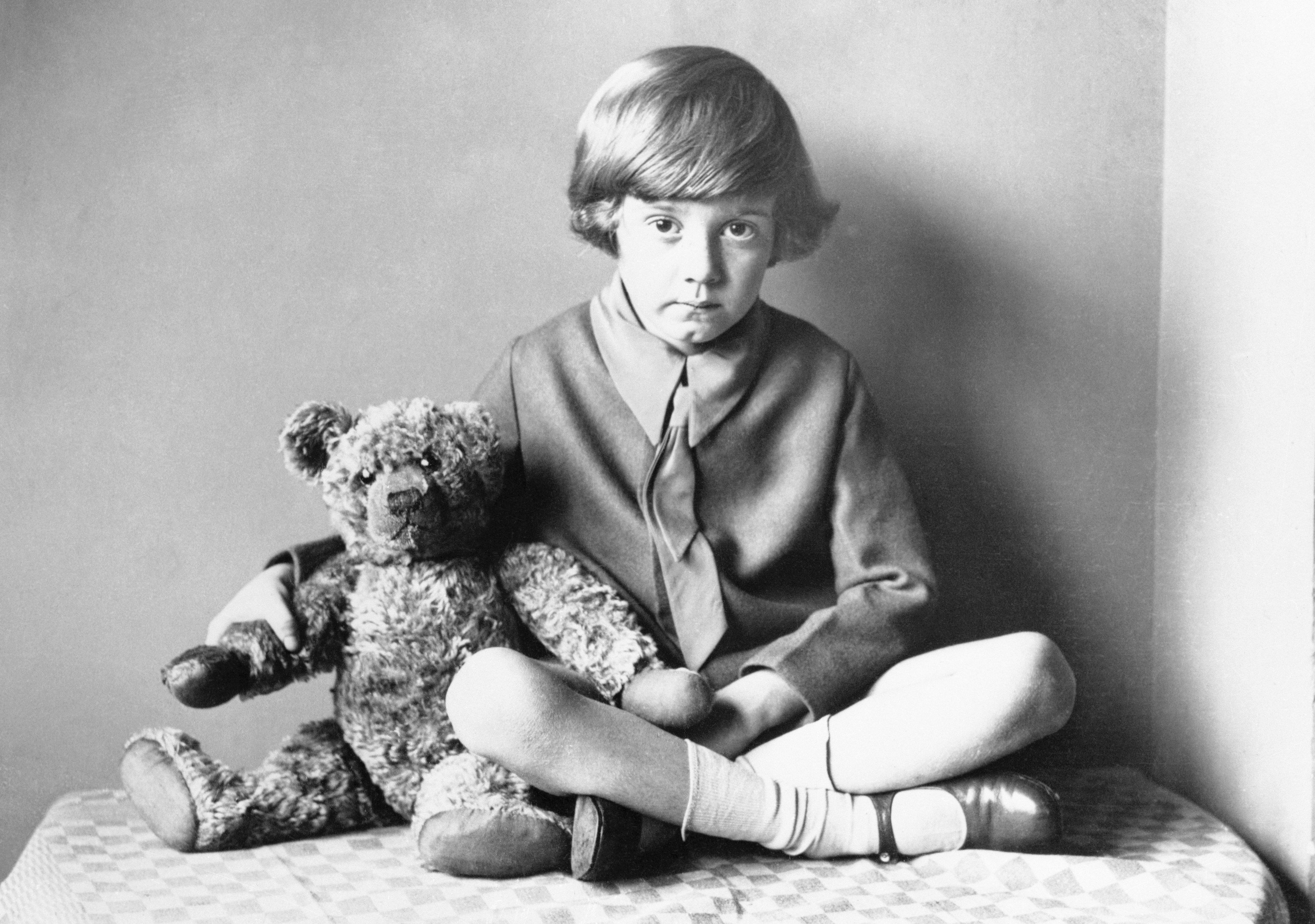 Winnie the Pooh Christopher Robin sitting at home with his teddy bear.