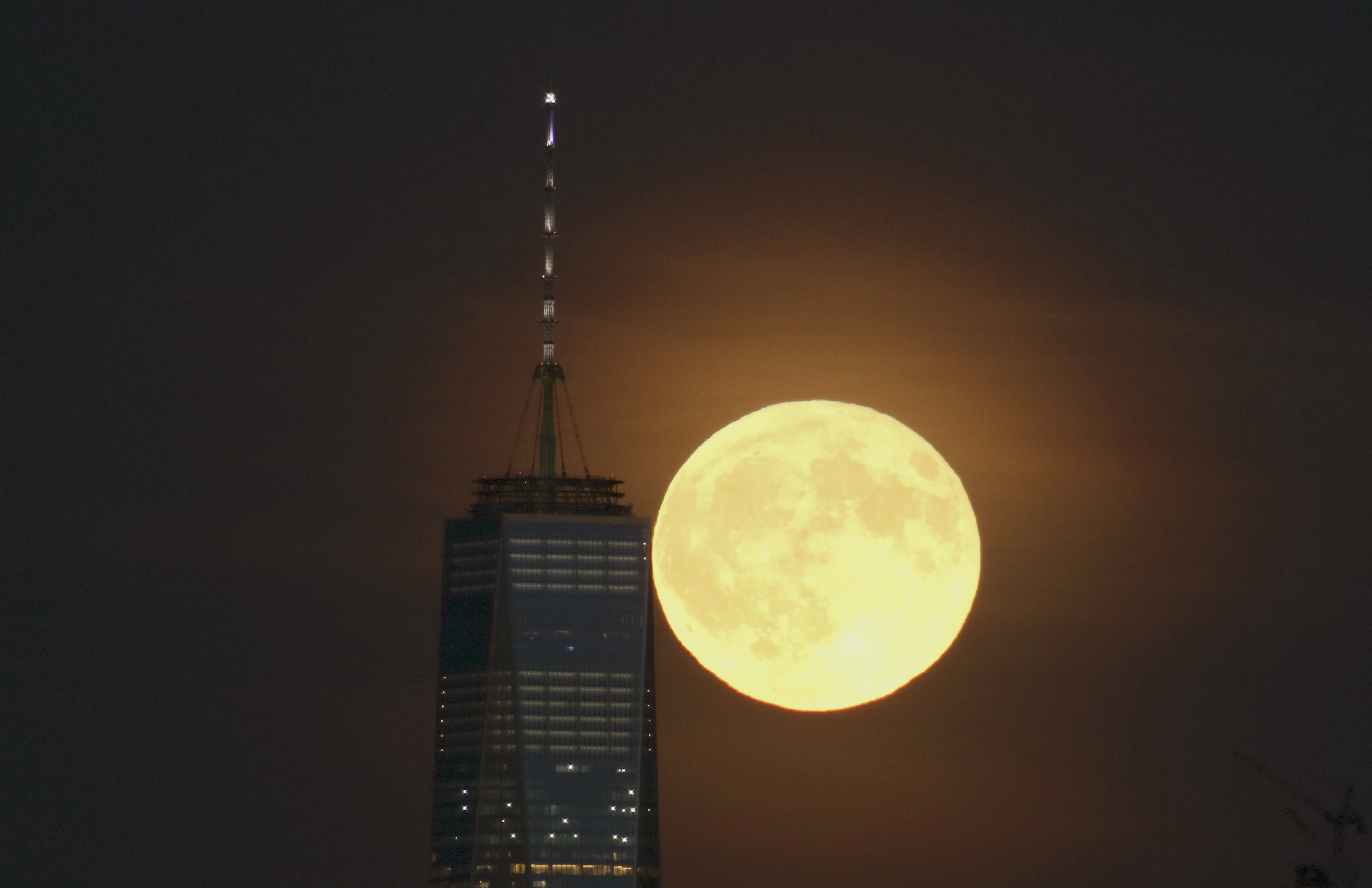 A full harvest moon rises behind Lower Manhattan and One World Trade Center in New York City on September 16, 2016 as seen from Newark, NJ.