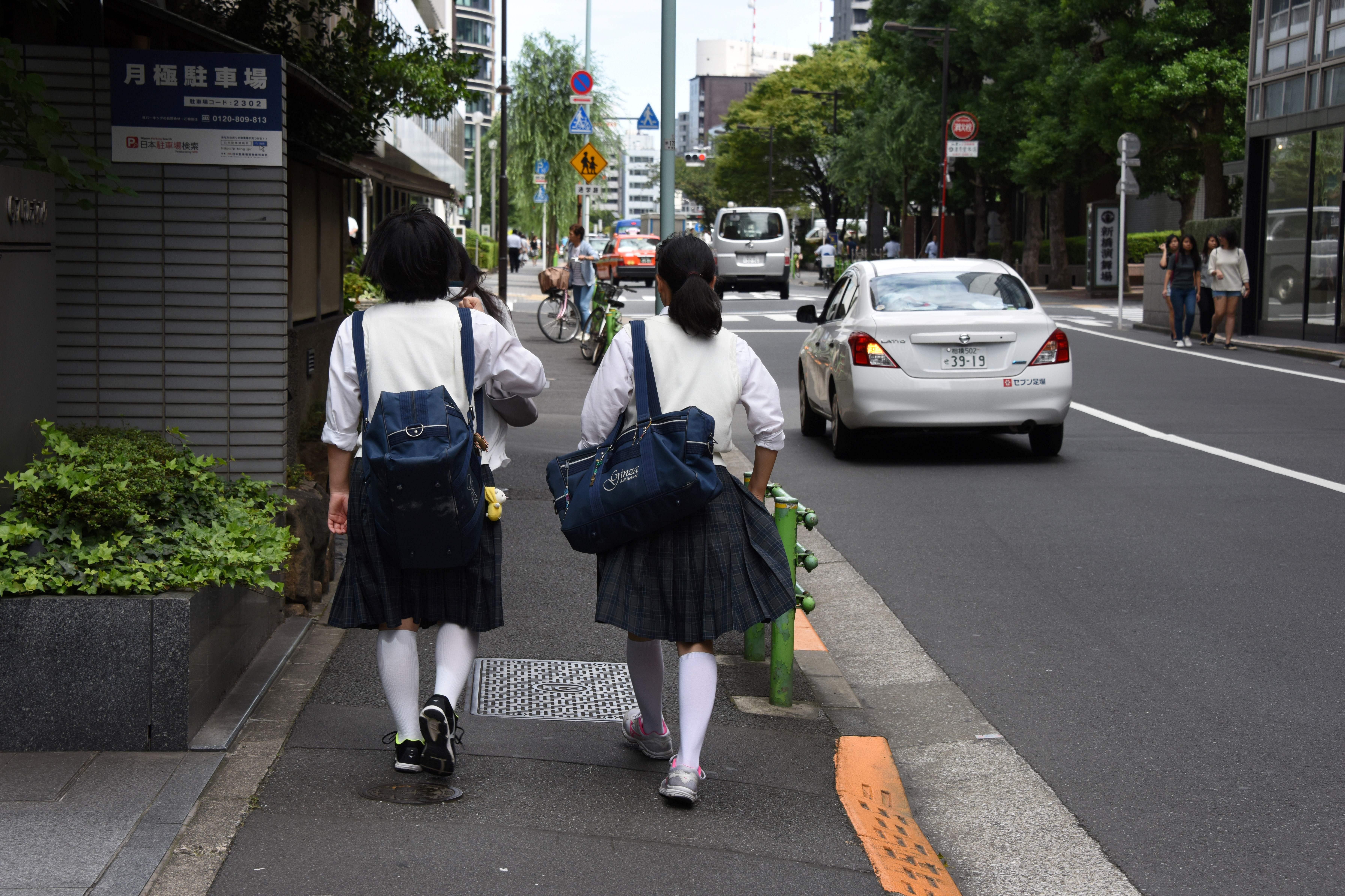 Japanese schoolgirls walk on a street in Tokyo on September 1, 2017.