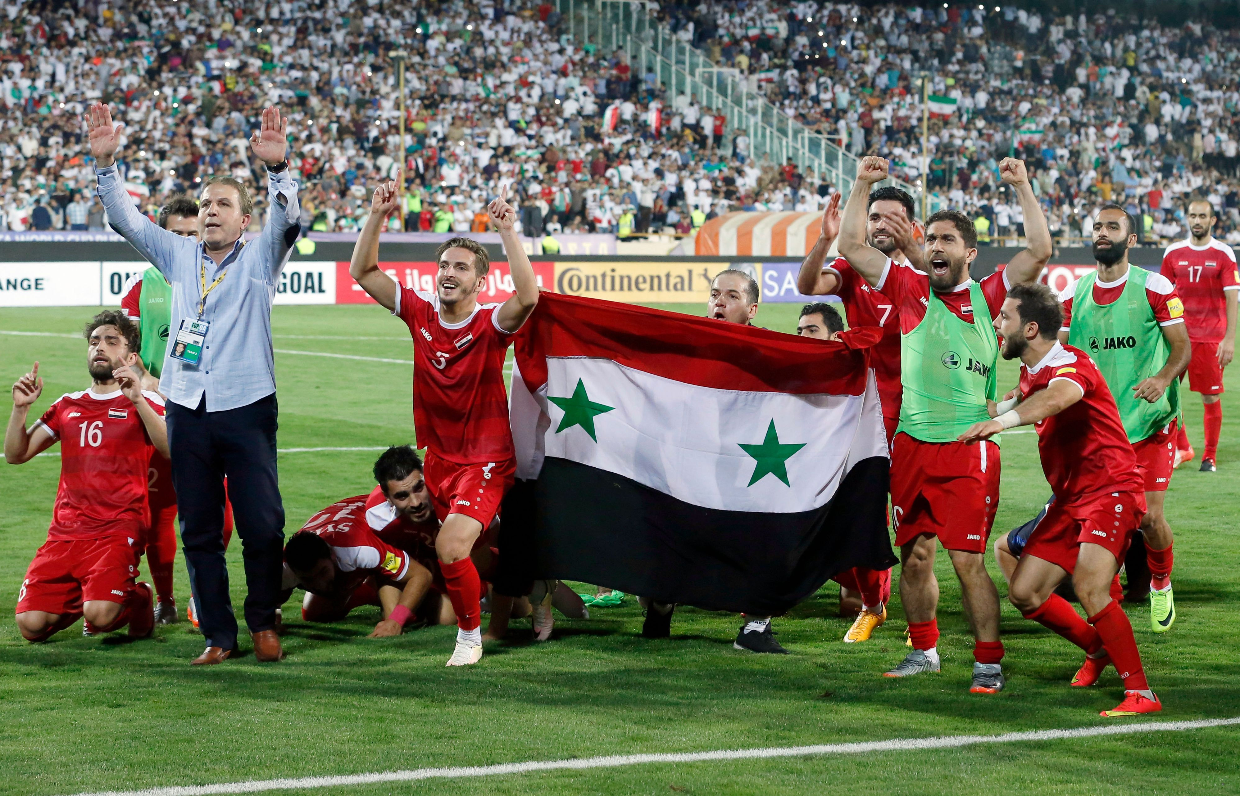 Syrian players celebrate after drawing a FIFA World Cup 2018 qualification match against Iran at Azadi Stadium in Tehran on Sept. 5, 2017.