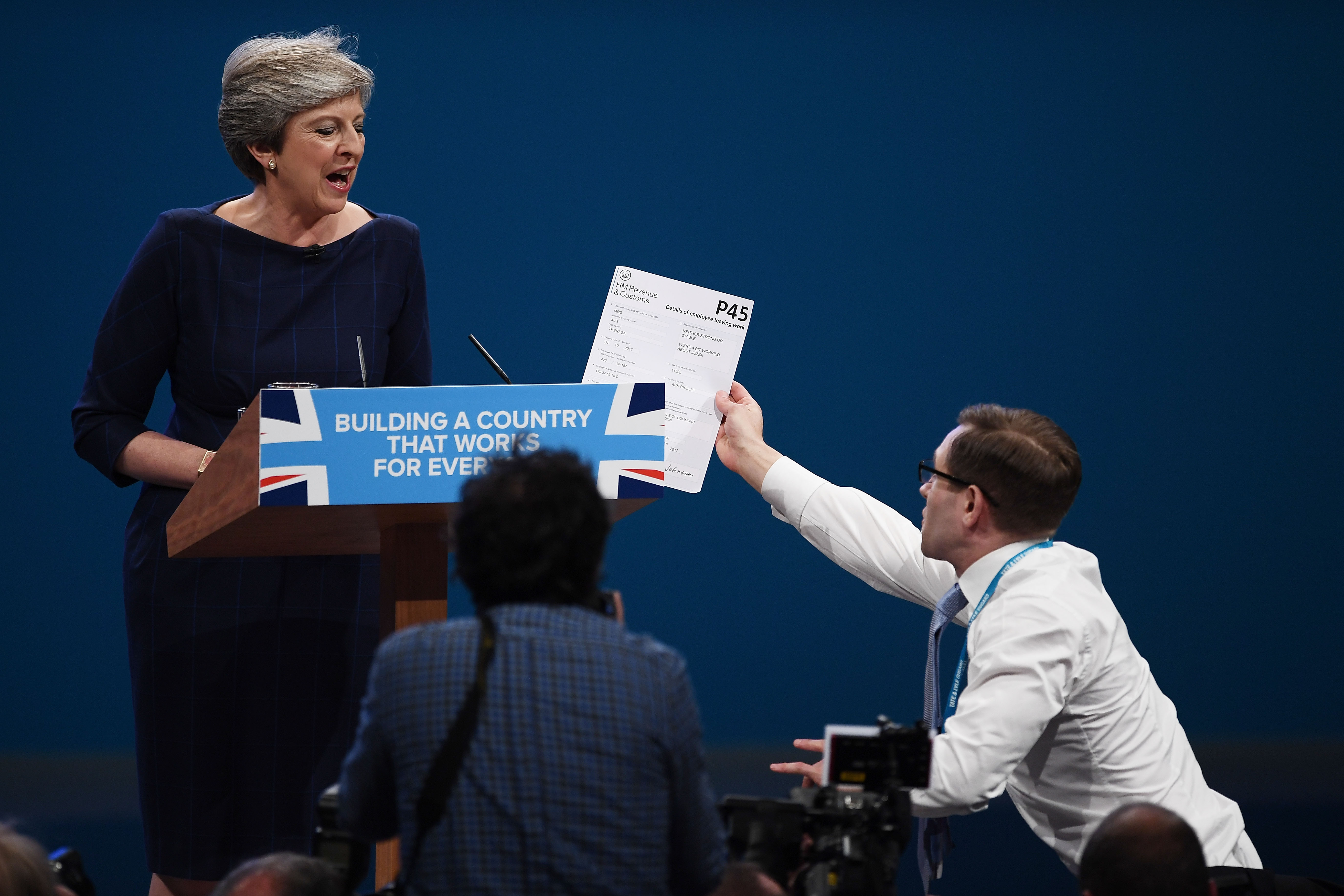 Comedian Simon Brodkin, aka prankster Lee Nelson, hands Prime Minister Theresa May a P45 during her keynote speech to delegates and party members on the last day of the Conservative Party Conference in Manchester on Oct. 4, 2017