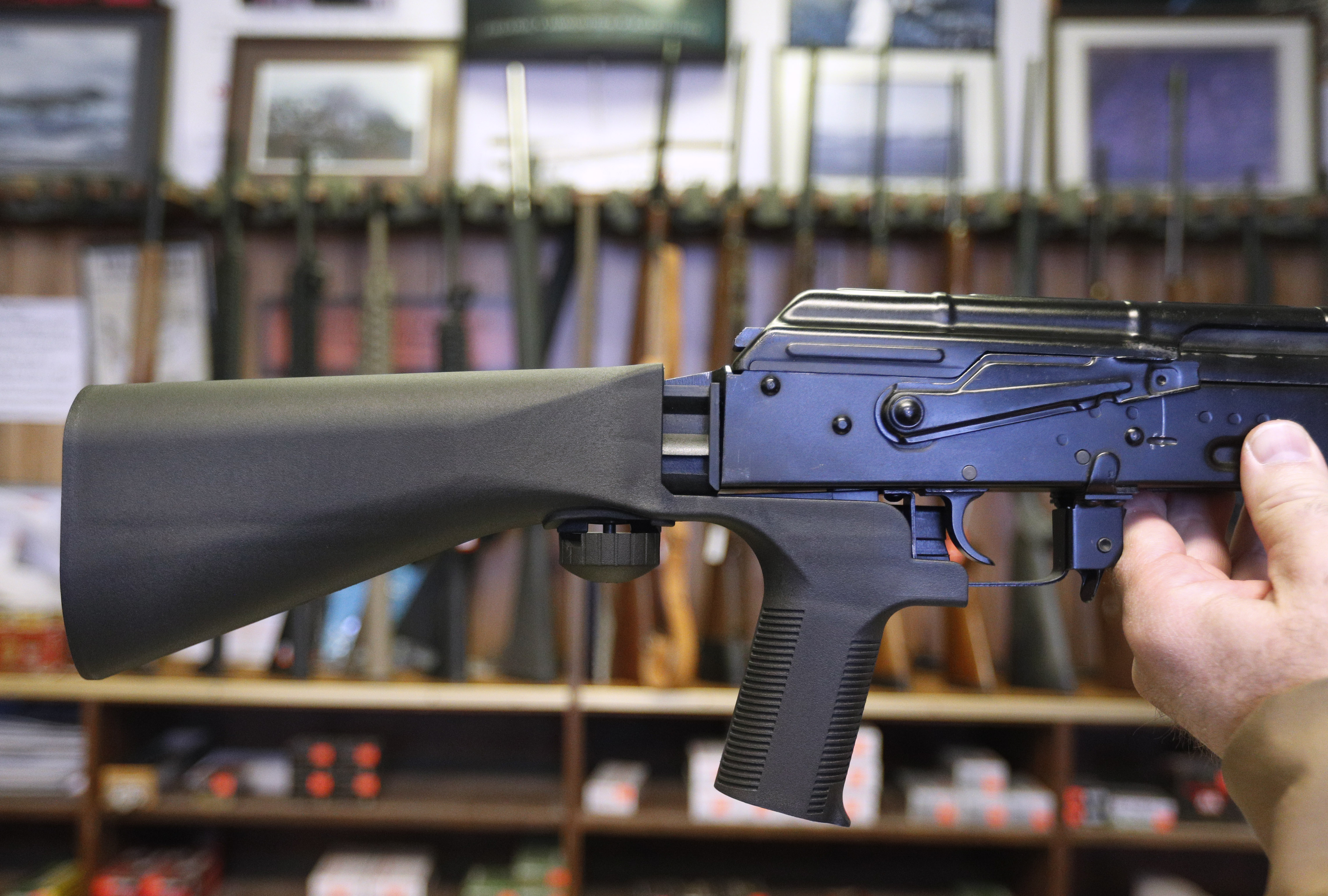 A bump stock device (left) that fits on a semi-automatic rifle to increase the firing speed, making it similar to a fully automatic rifle, is installed on a AK-47 semi-automatic rifle at a gun store on October 5, 2017 in Salt Lake City, Utah.