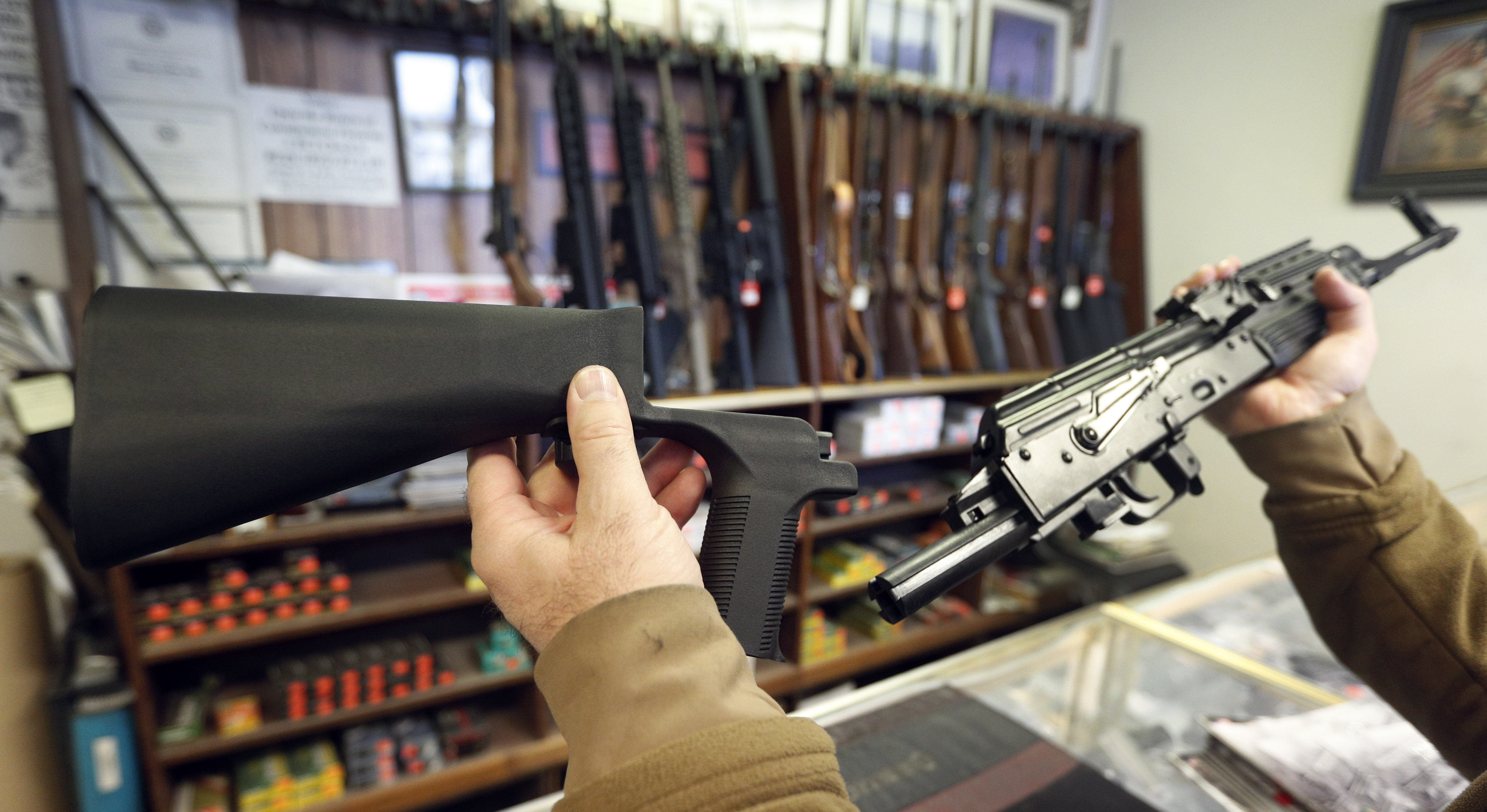 A bump stock device, (left) that fits on a semi-automatic rifle to increase the firing speed, making it similar to a fully automatic rifle, is shown next to a AK-47 semi-automatic rifle, (right) at a gun store on October 5, 2017 in Salt Lake City, Utah.