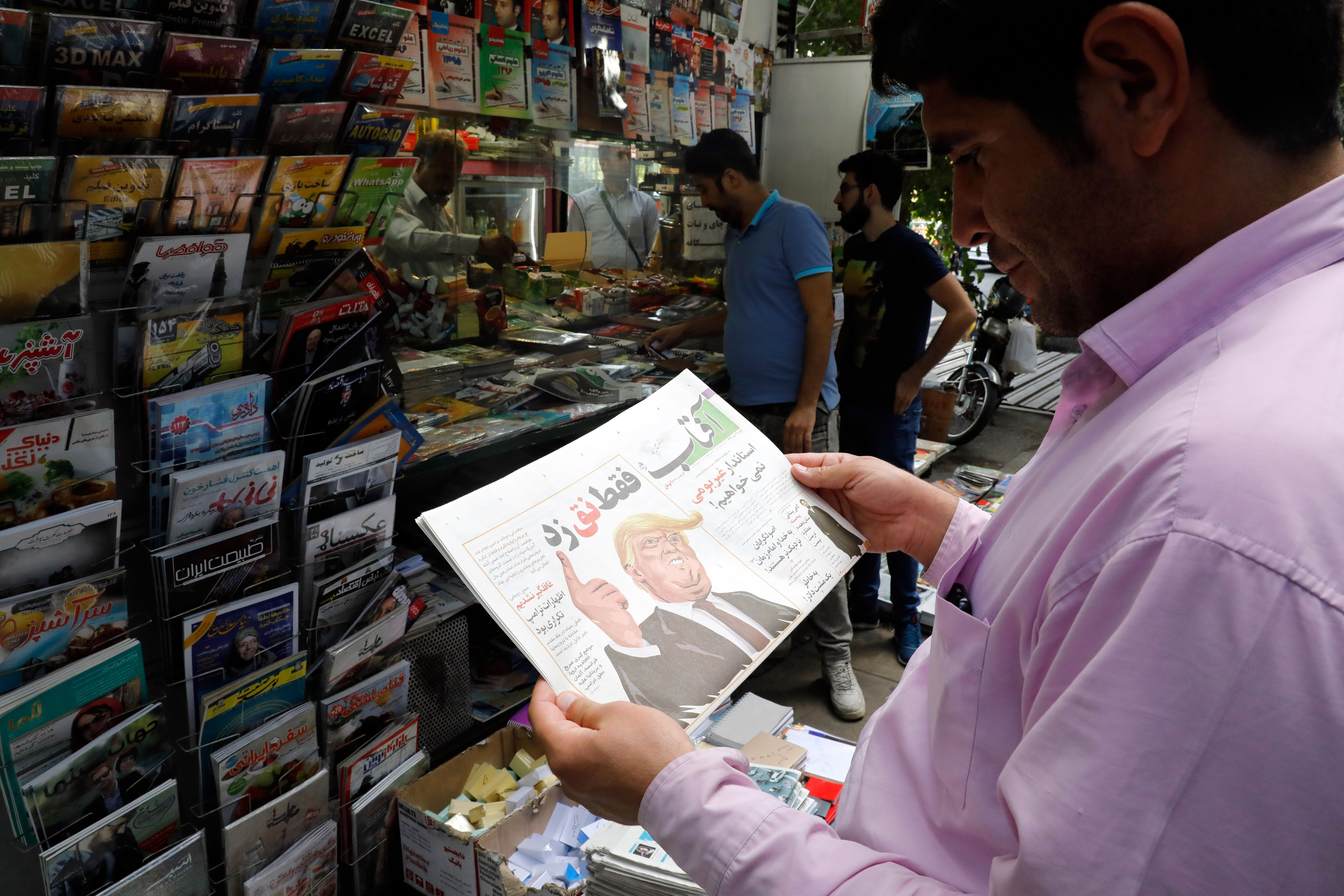 An Iranian man reads a copy of the daily newspaper 'Aftab' bearing a caricature of US President Donald Trump with a headline that reads in Persian  He just nagged , on Oct. 14, 2017 in the capital Tehran