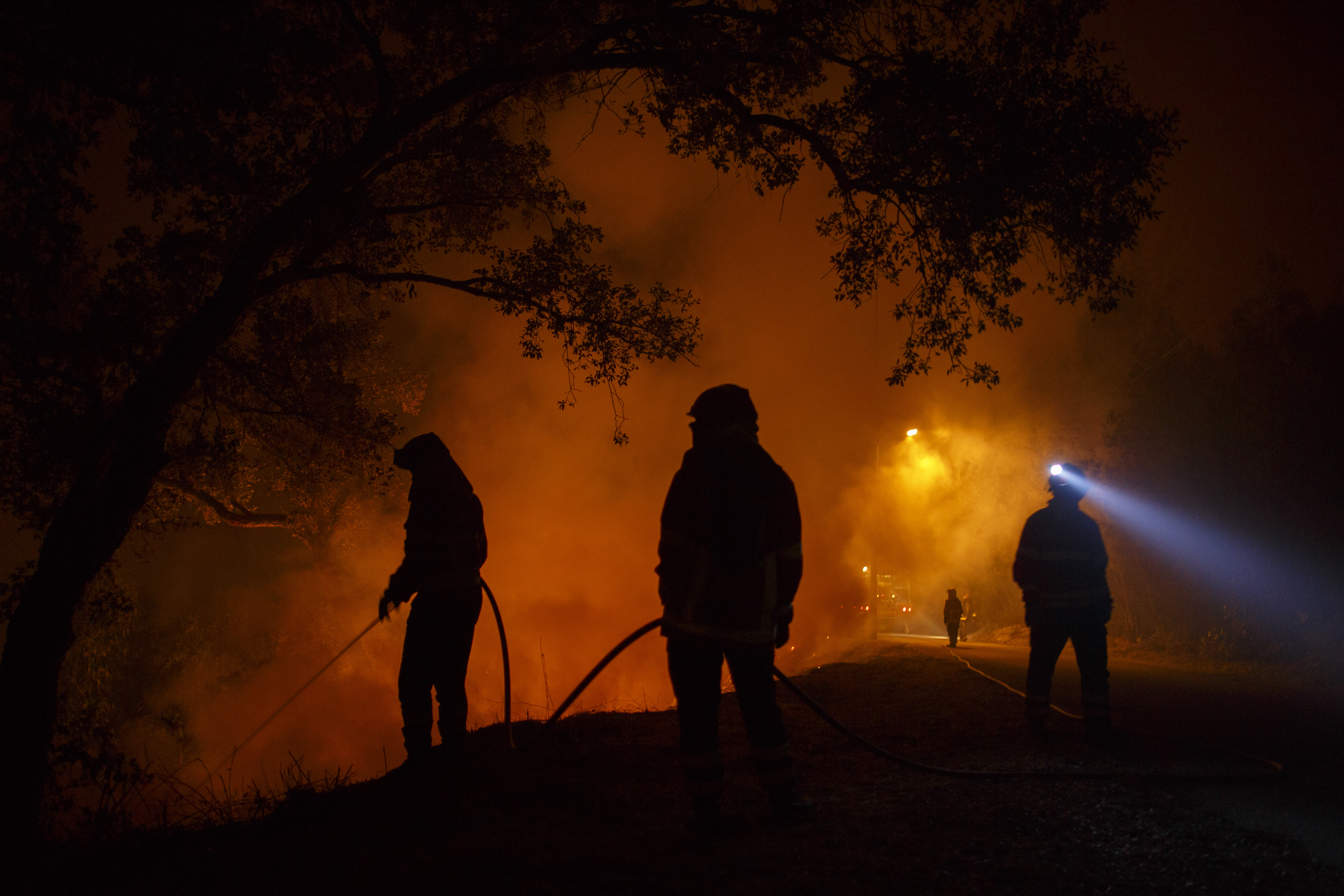 Firefighters battle a forest wildfire at Vilarinho village, near Lousa, on October 16, 2017 in the Coimbra region of Portugal.
