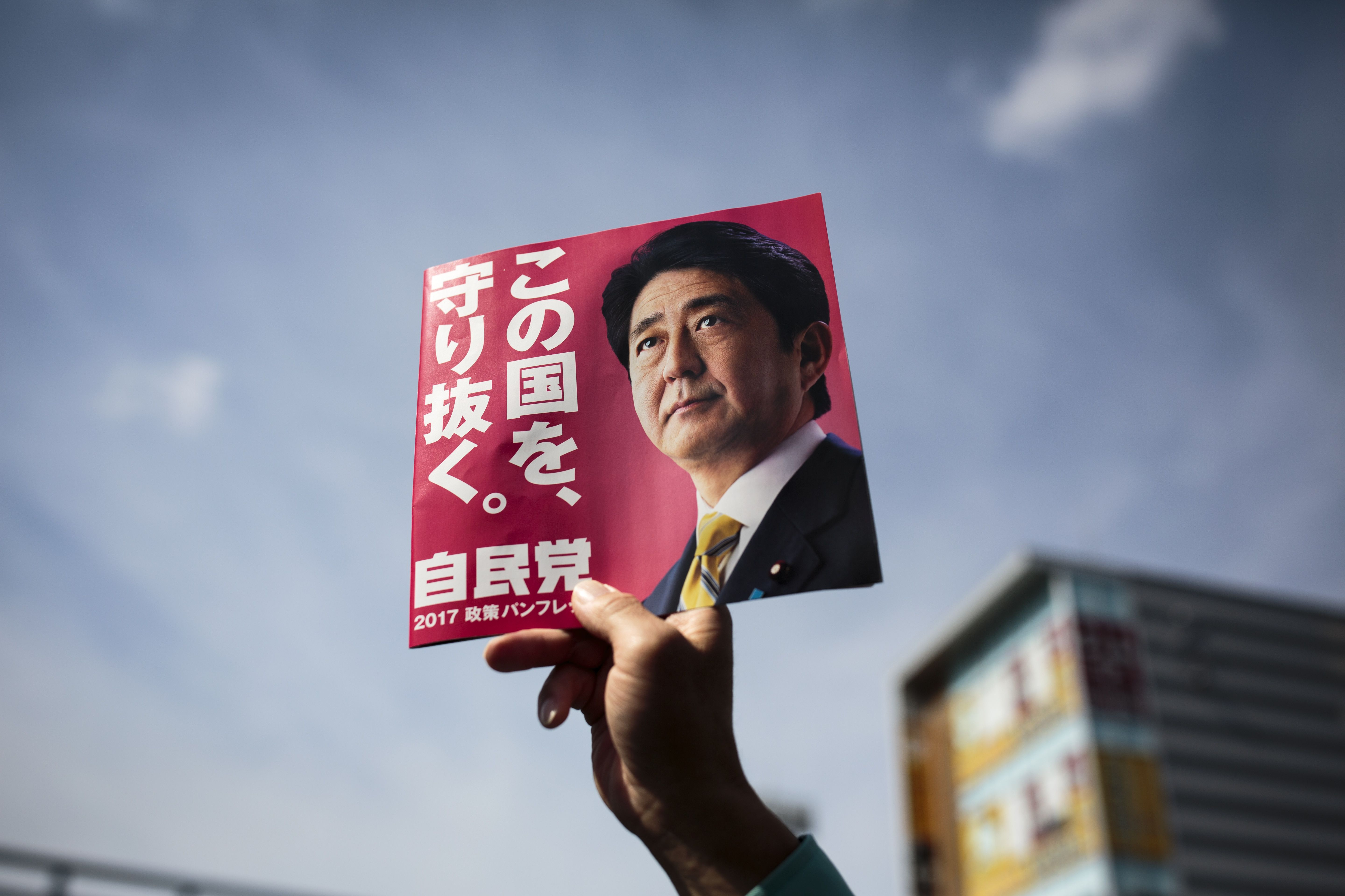 In this picture taken on October 18, 2017, a man holds an electoral leaflet showing Japan's Prime Minister and ruling Liberal Democratic Party (LDP) president Shinzo Abe during an election campaign in Saitama.