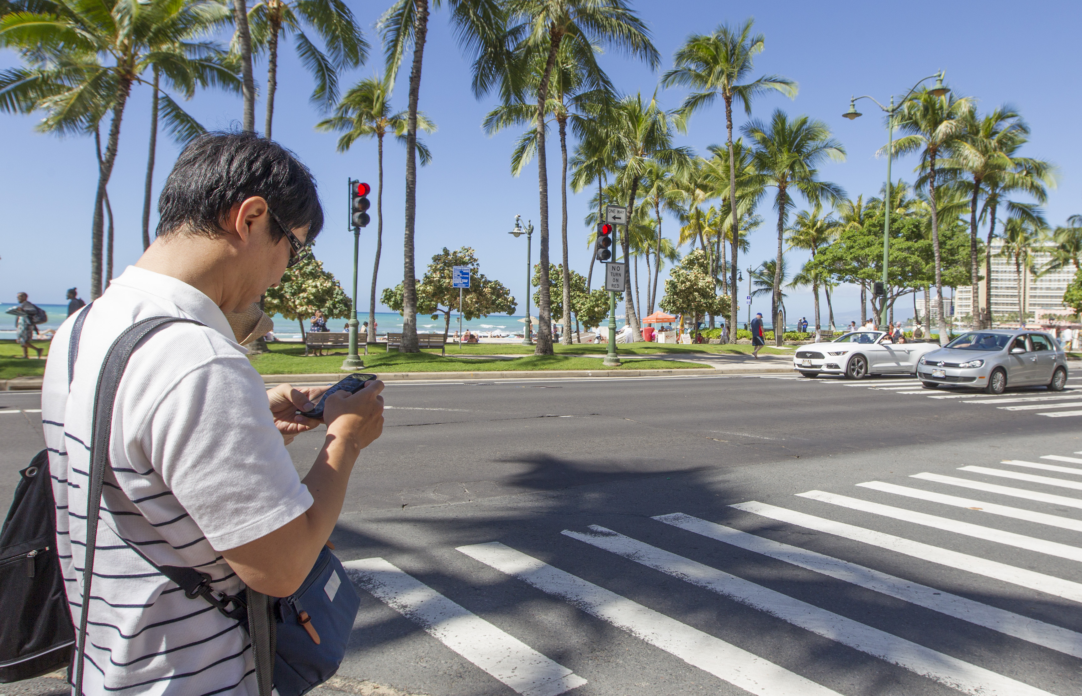 A visitor texts before crossing the street in Waikiki Tuesday, October 24, 2017 in Honolulu, Hawaii.                    The Honolulu Police Department will start enforcing The City and County of Honolulu's newest law against looking or texting on your cell phone while using a crosswalk.
