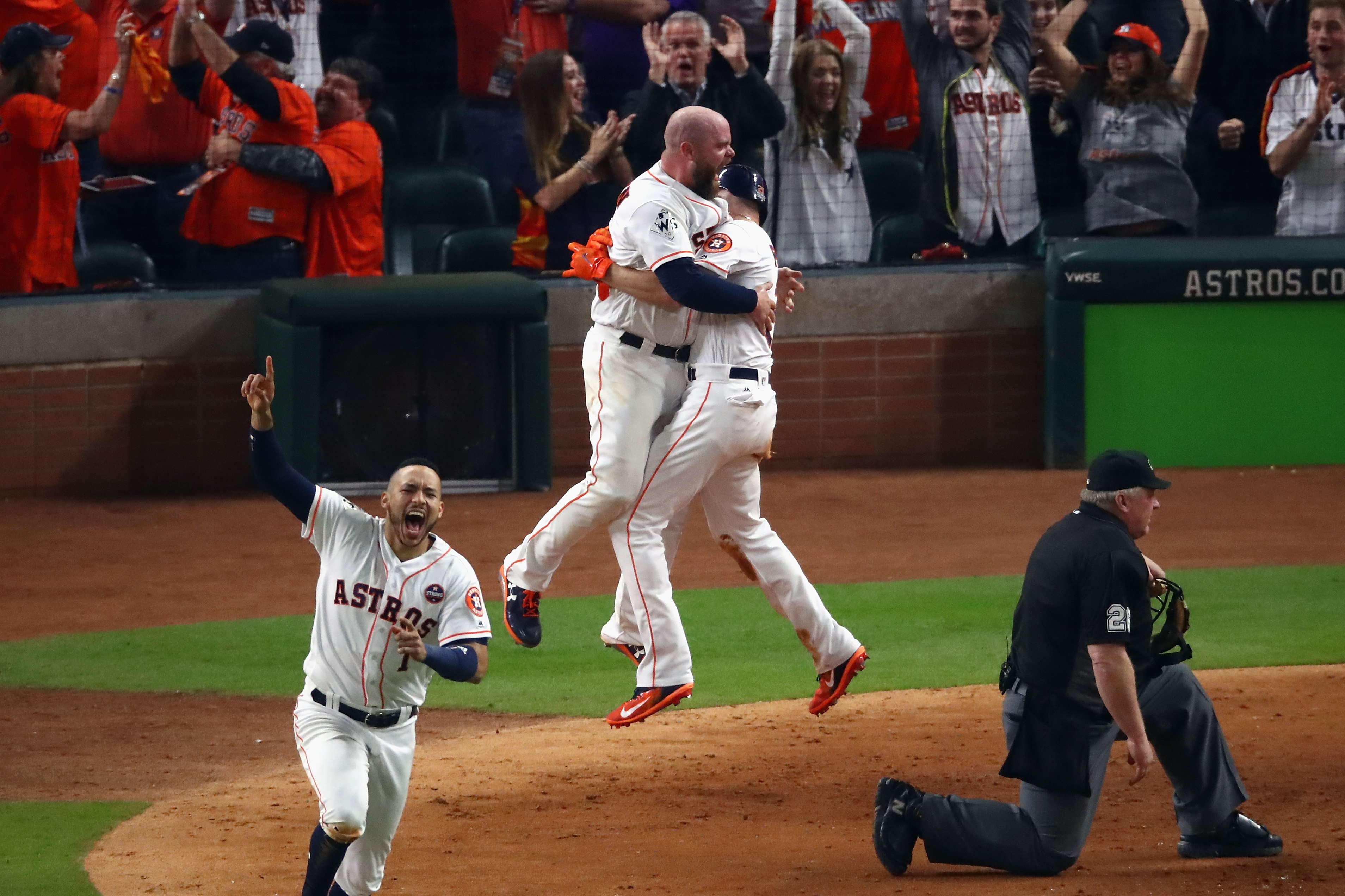 Derek Fisher of the Houston Astros celebrates with Brian McCann after scoring the winning run during the tenth inning against the Los Angeles Dodgers in game five of the 2017 World Series in Houston, Texas on October 30, 2017.