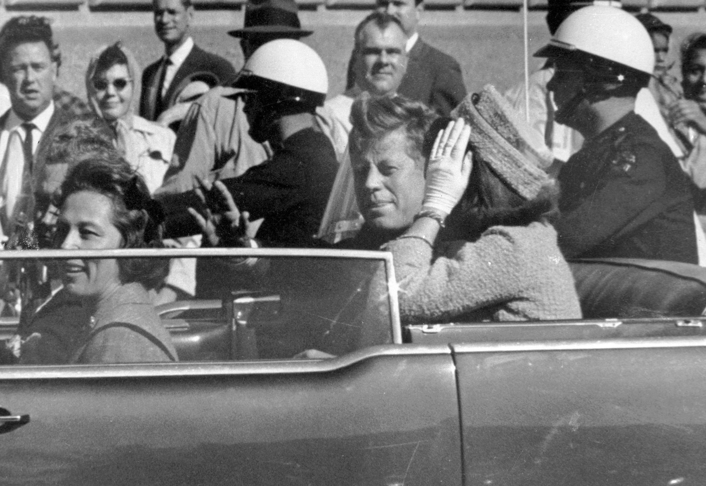President John F. Kennedy waves from his car in a motorcade in Dallas on Nov. 22, 1963.