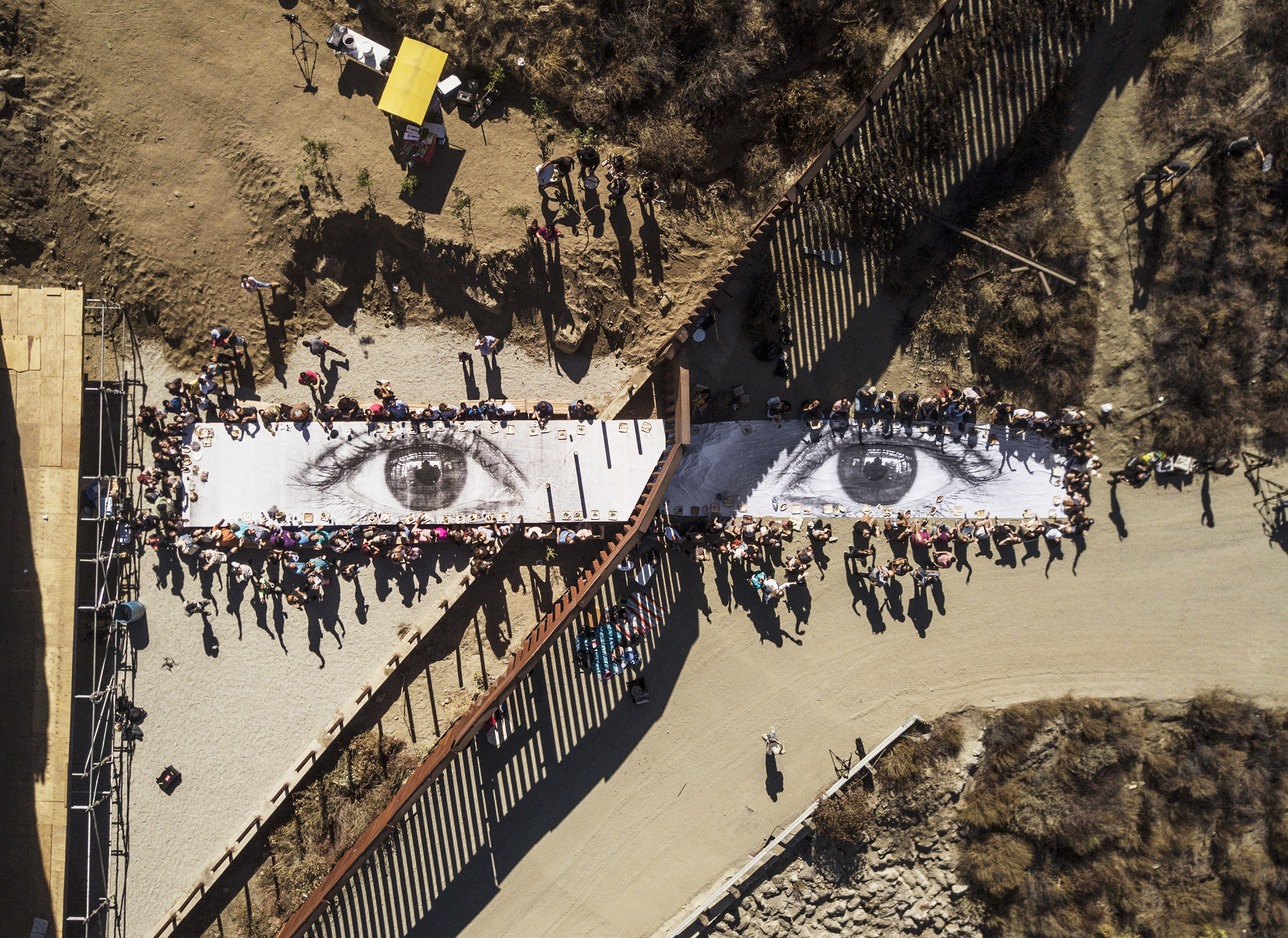 A picnic takes place on JR's Giant Picnic, a photograph of the eyes of a Dreamer at the U.S.-Mexico border in Tecate, Mexico, on Oct. 8
